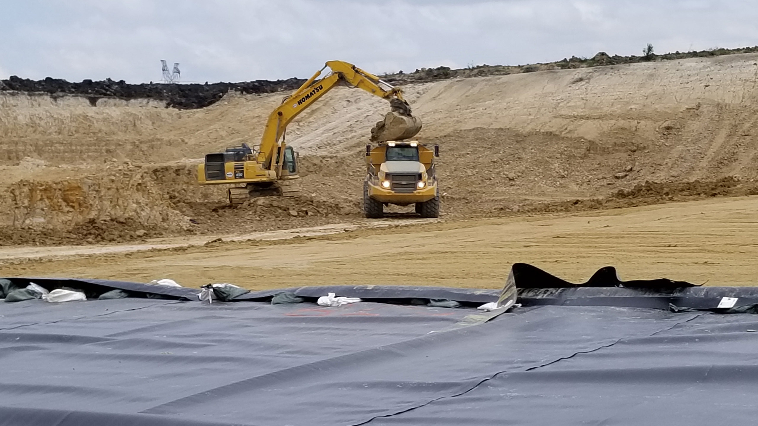 Crews work quickly using an excavator to clear out more dirt from the base of the new landfill section and place the dirt onto a large yellow dump truck.