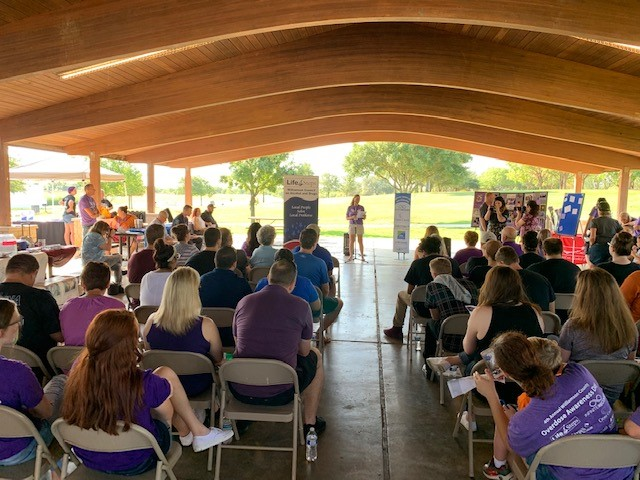 A speaker stands before a large crowd attending Overdose Awareness Day at the Lakeview Pavilion at Old Settlers Park in Round Rock.
