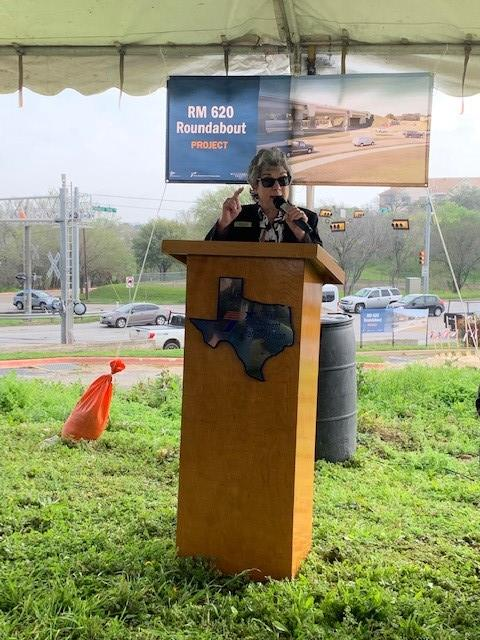 Commissioner Cook delivers some remarks at the podium under a carp at the RM 620 Roundabout site and then recites her poem.