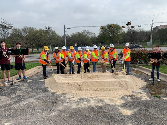 Officials with the City of Round Rock, the Texas Department of Transportation, and Williamson County dig their shovels into the dirt as members of the Round Rock High School band stand by.