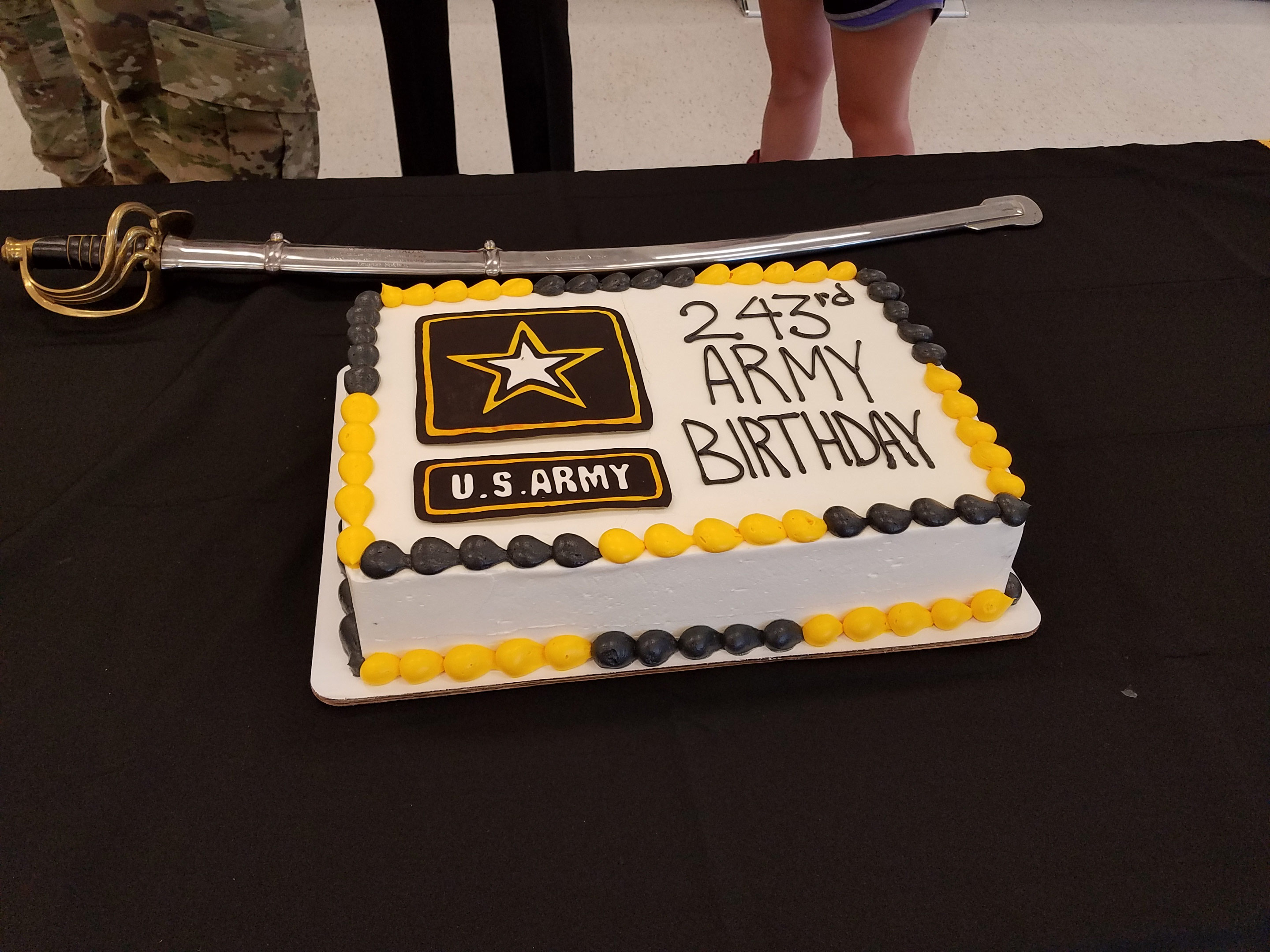 The Army birthday cake and saber lying beside it.