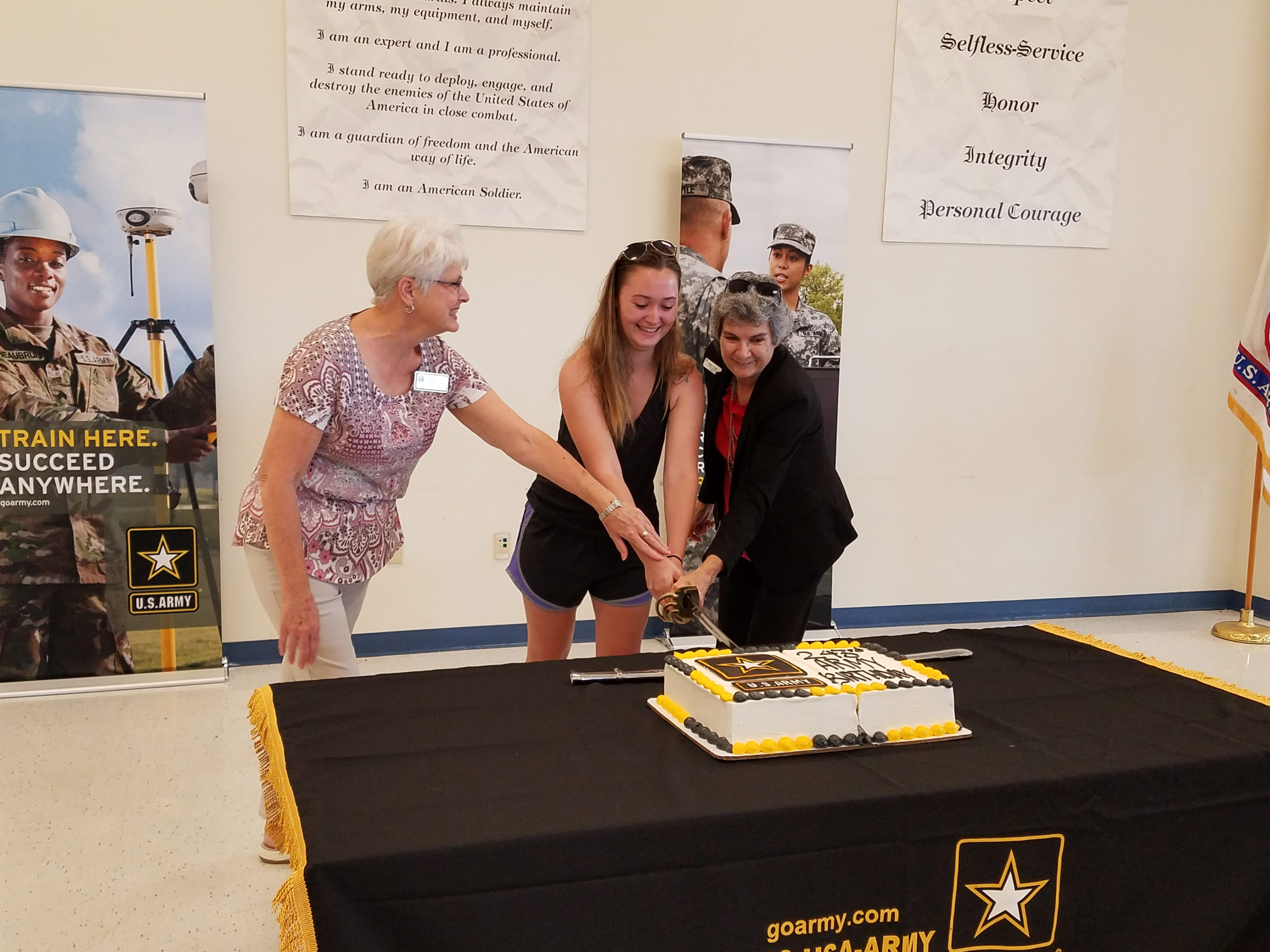 Commissioner Cook (center) gets help from (left) Debra Babcock with Commissioner Covey's (Pct. 3) Office and (right) Private Lydia Byrns as all three hold the saber to cut the Army birthday cake.