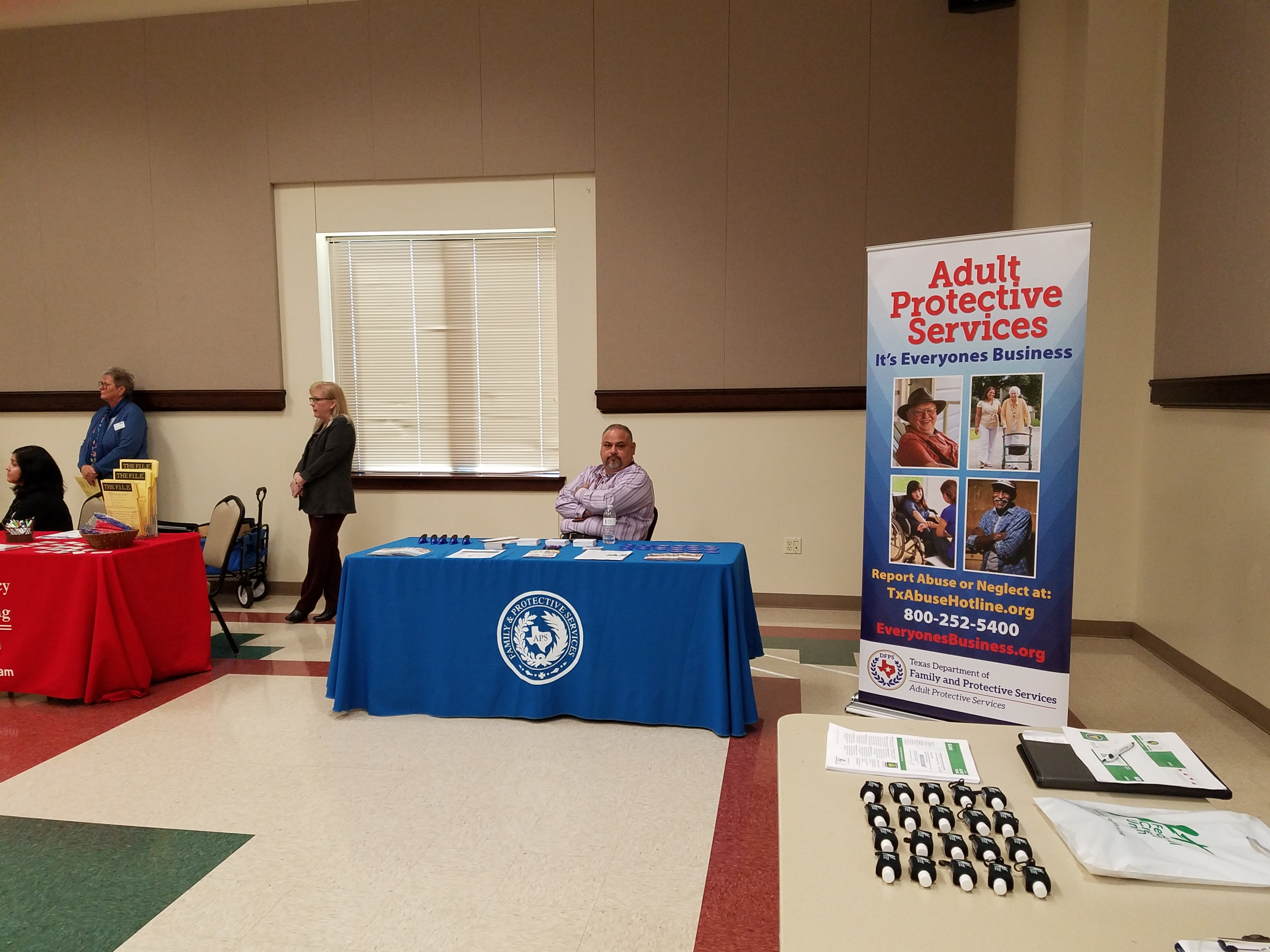 Samuel Cortina with Adult Protective Services sits at his display table awaiting his turn to speak on what services his agency provides when someone is a victim of fraud.