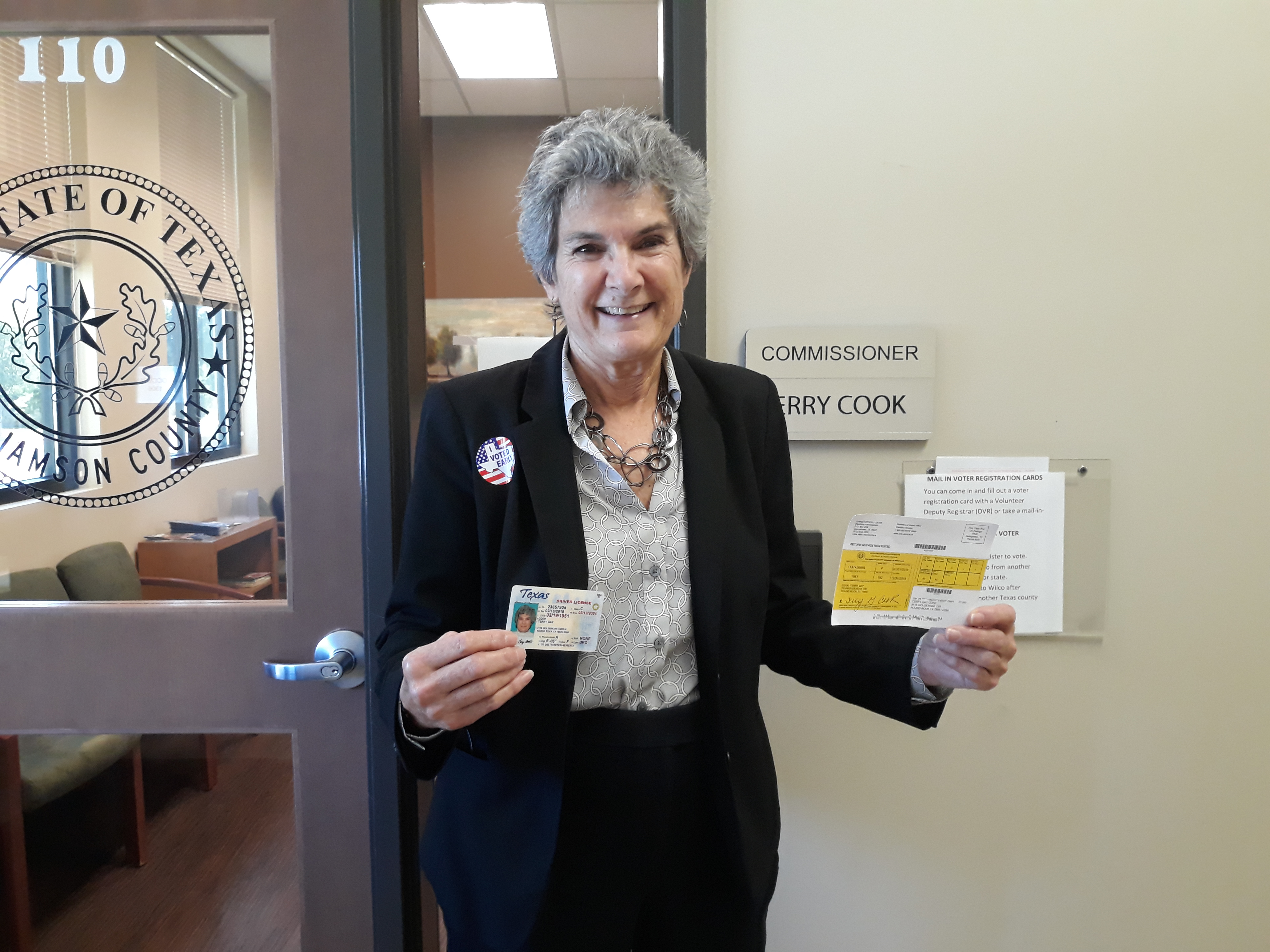 Commissioner Cook holds up her voter registration card and driver's license after she cast her vote on the first day of early voting at the Precinct 1 Jester Annex in Round Rock.