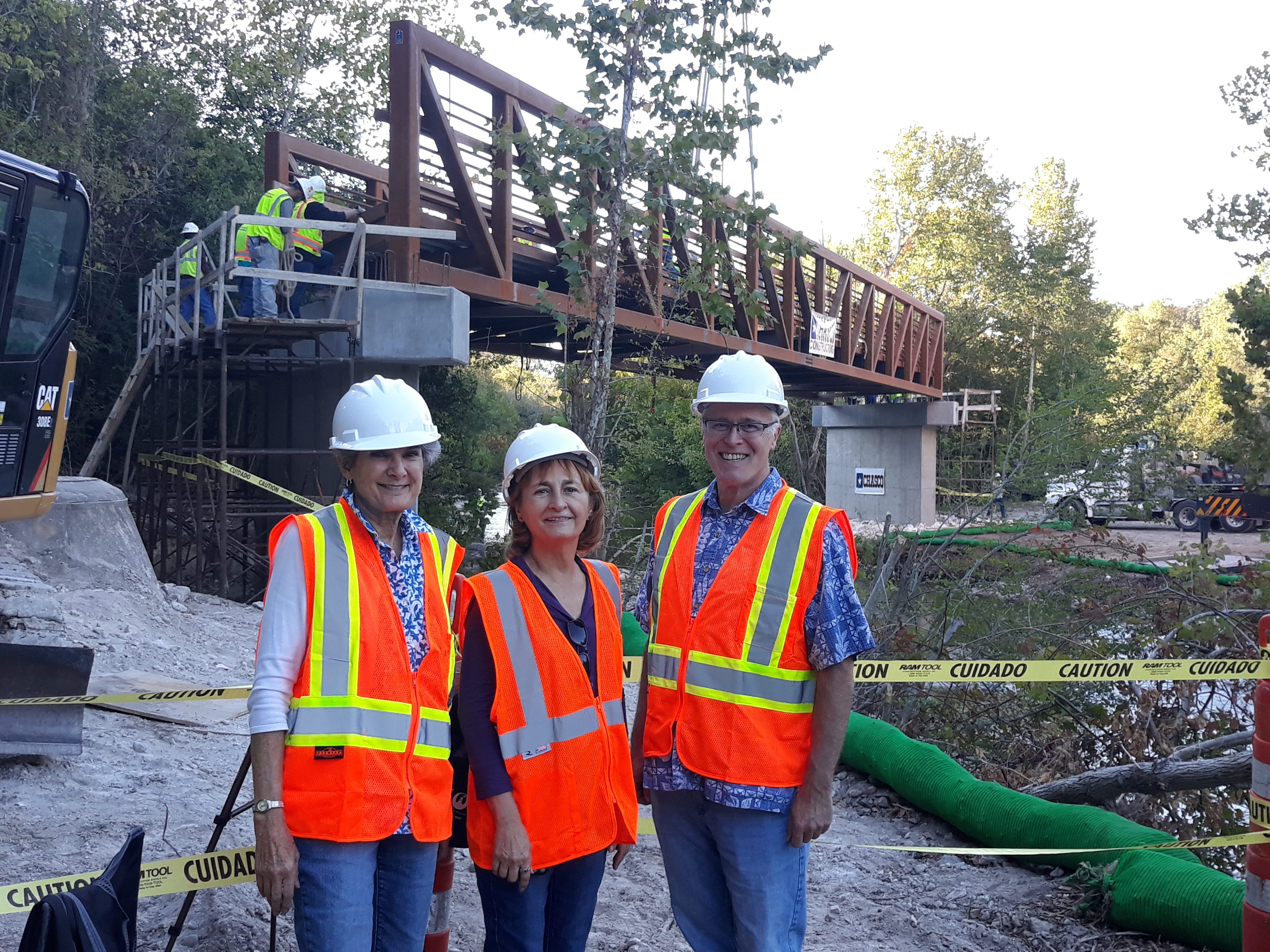 Commissioner Cook and staff Doris Sanchez and Garry Brown pose in front of the bridge after it was lowered onto the structures.
