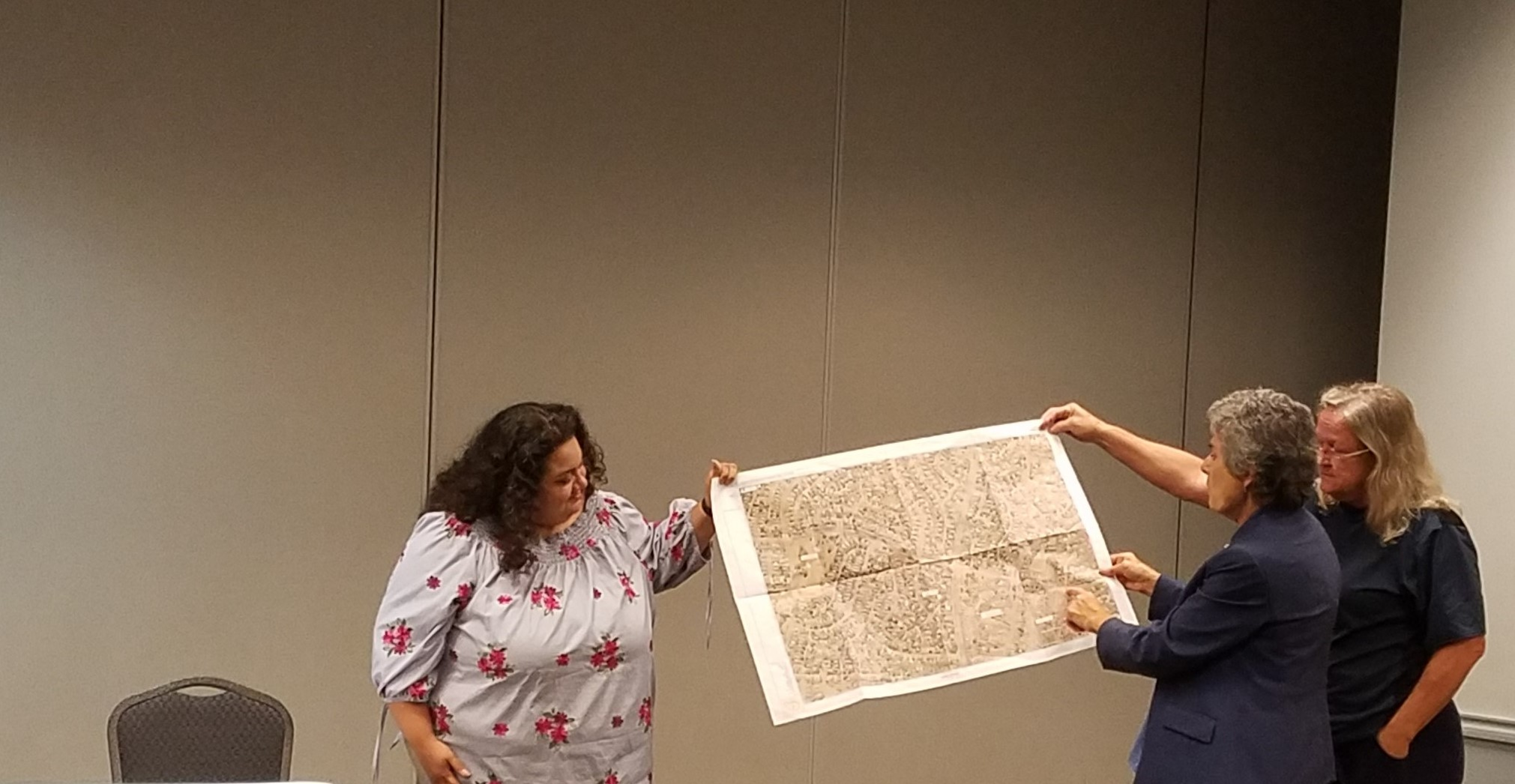 A Board member and resident help Commissioner Cook hold up an area map while she explains current and projected road projects.