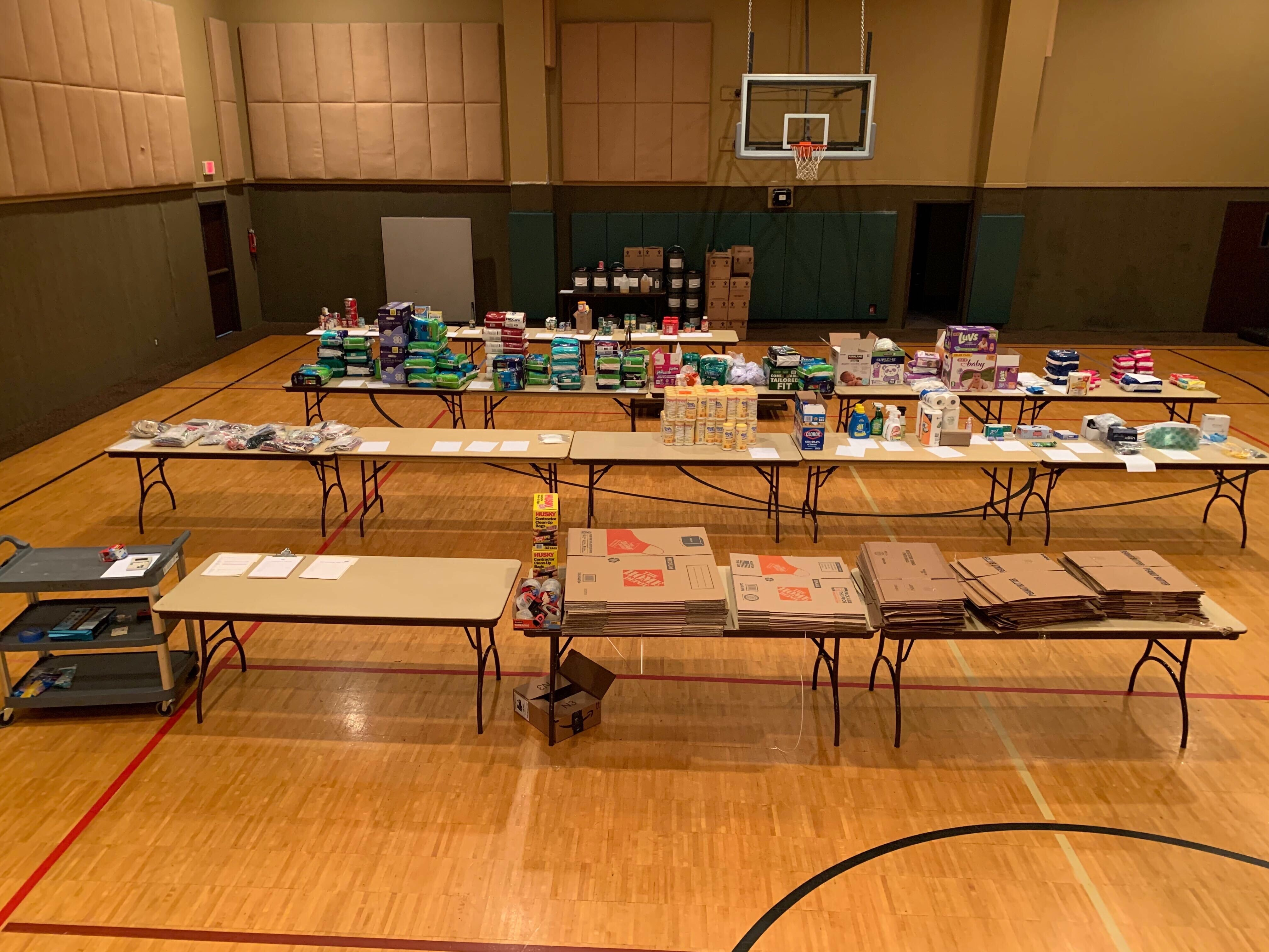 Supplies are neatly arranged in stacks on tables at the warehouse set up at the First Baptist Church in Georgetown ready for pick-up and delivery by volunteers.