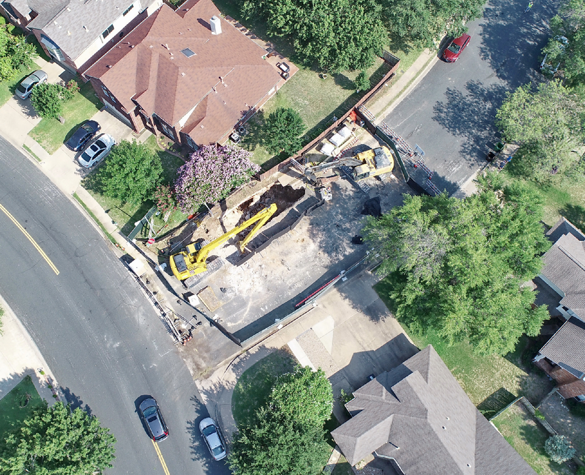 An aerial view taken from a drone of the homes and the sectioned-off area around the Cambria Cave excavation.