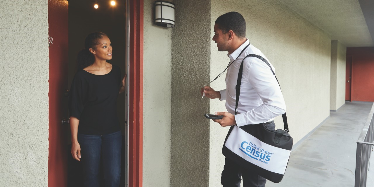 NACo County News stock photo of a woman opening her door to a Census worker.