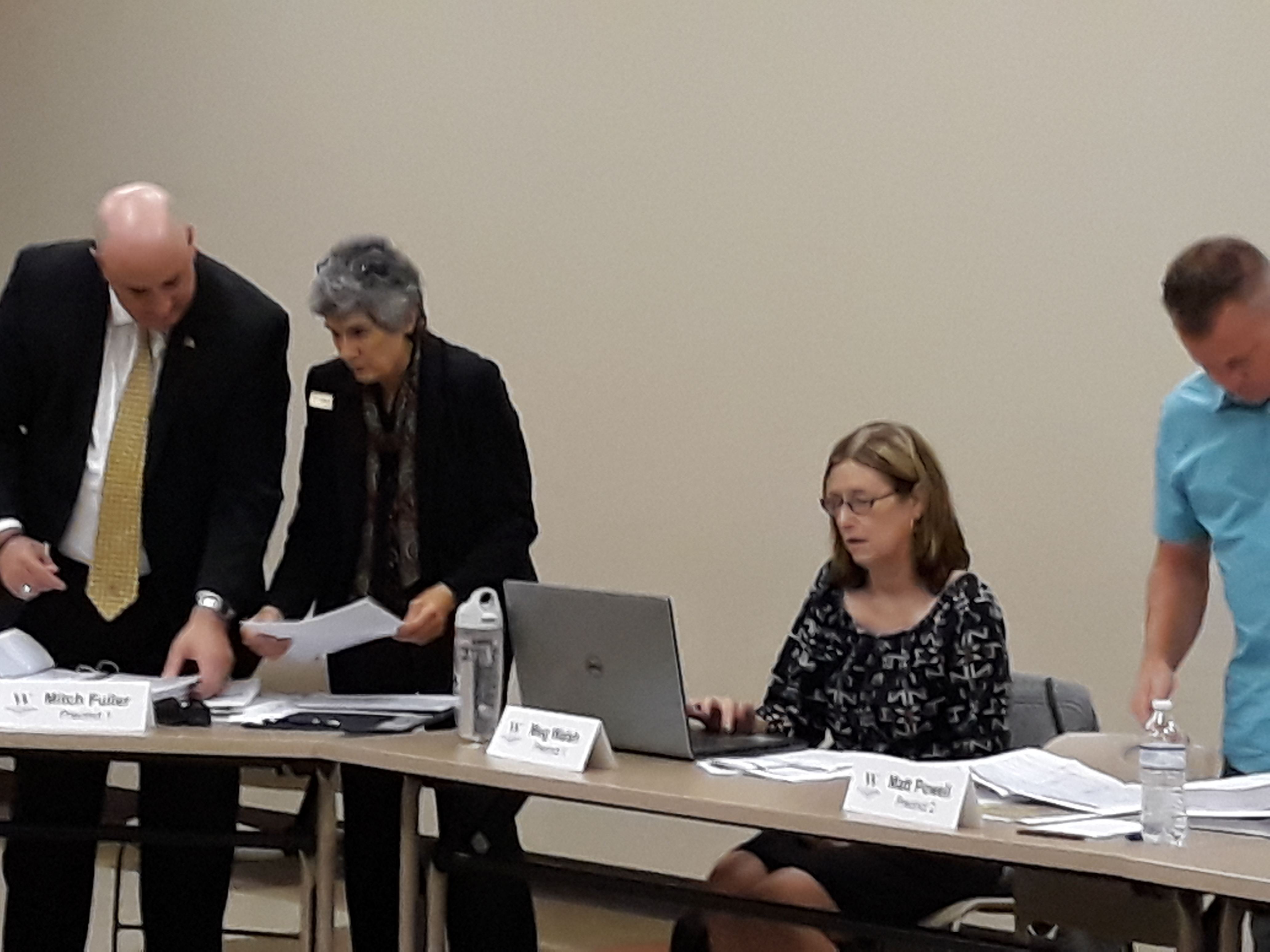 Commissioner Cook reviews documents on projects with Committee member Mitch Fuller, Pct. 1; seated is Meg Walsh, Pct. 1 and standing next to her is Joe Bob Ellison, Pct. 2 member.