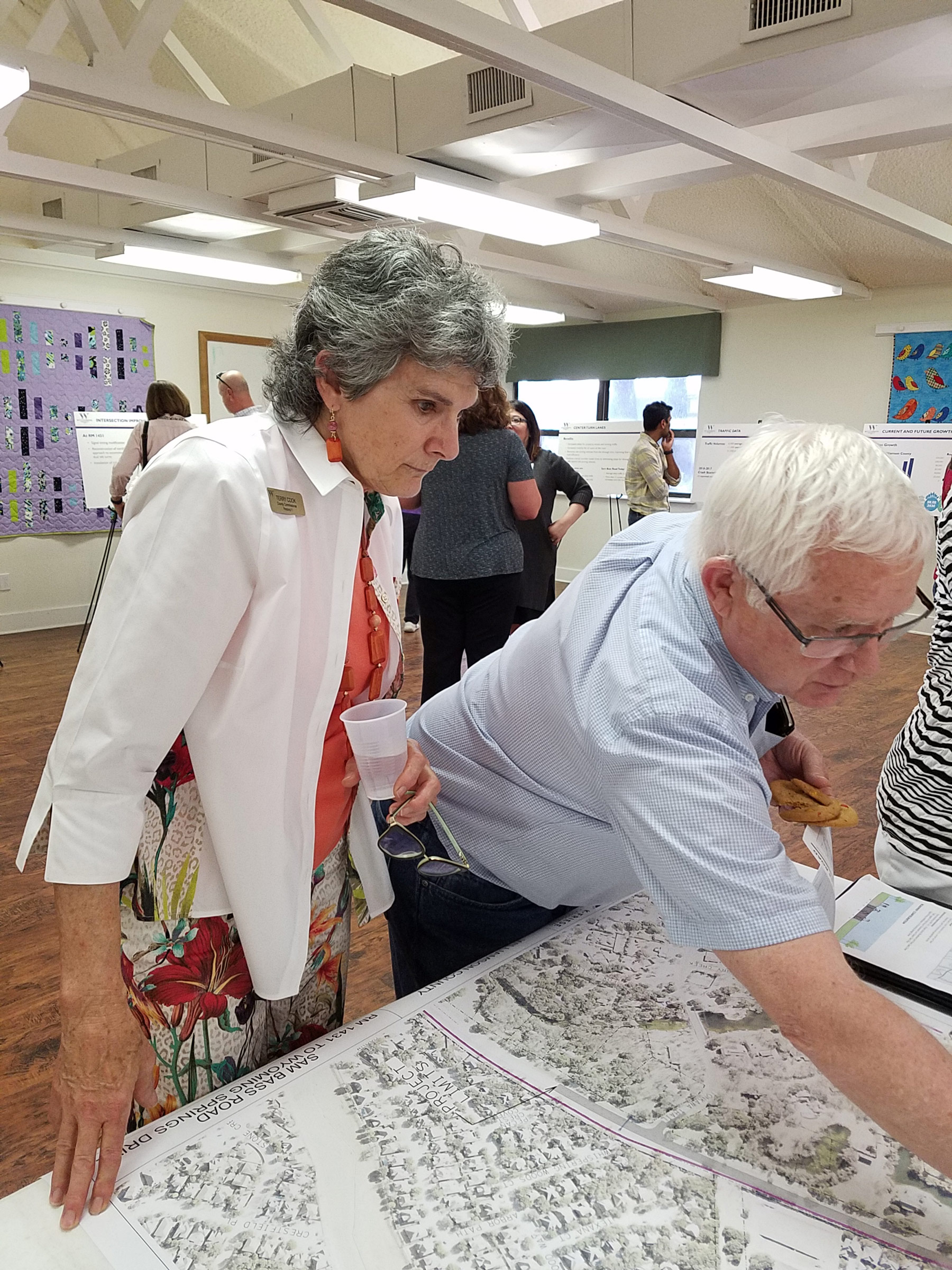 Commissioner Cook studies a map of the proposed Corridor H improvement with a resident.