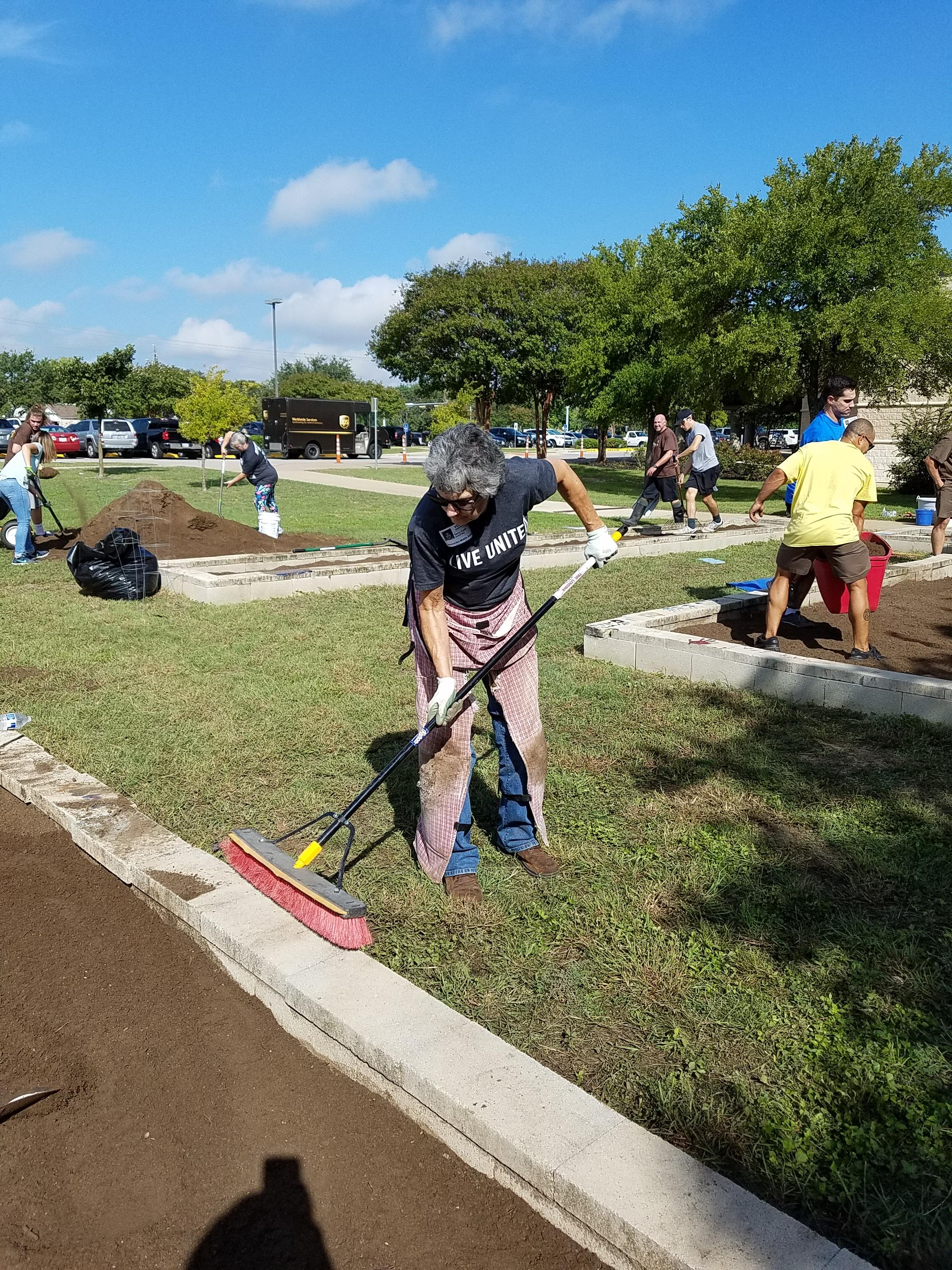 Commissioner Cook sweeps the edges of the raised beds after the topsoil was placed in each.