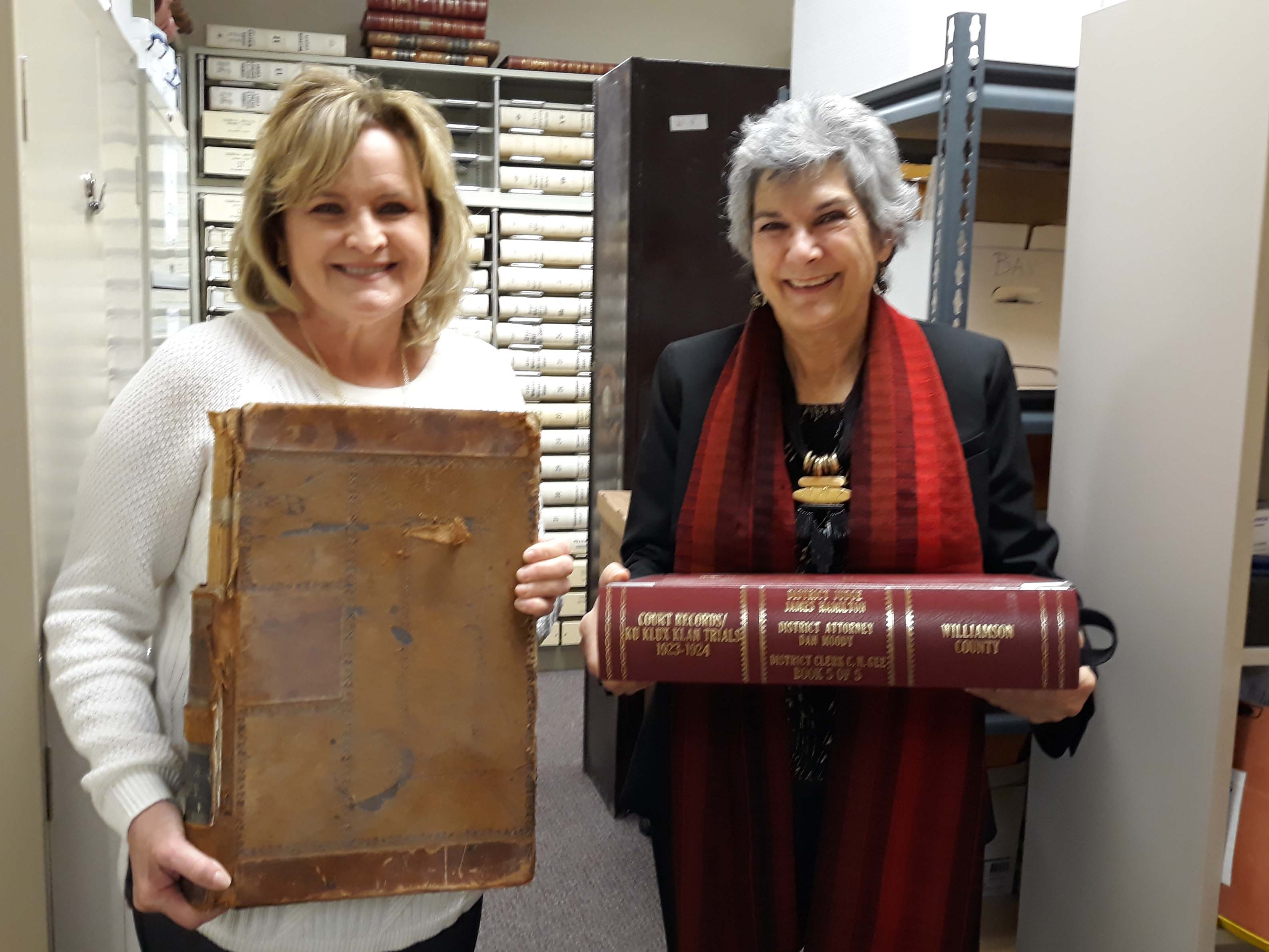 District Clerk Lisa David holds up a historical court file that has not yet been preserved and Commissioner Cook is holding a preserved record of the Ku Klux Klan Trials prosecuted by then District Attorney Dan Moody from 1923-24, who later became Texas' youngest Governor.