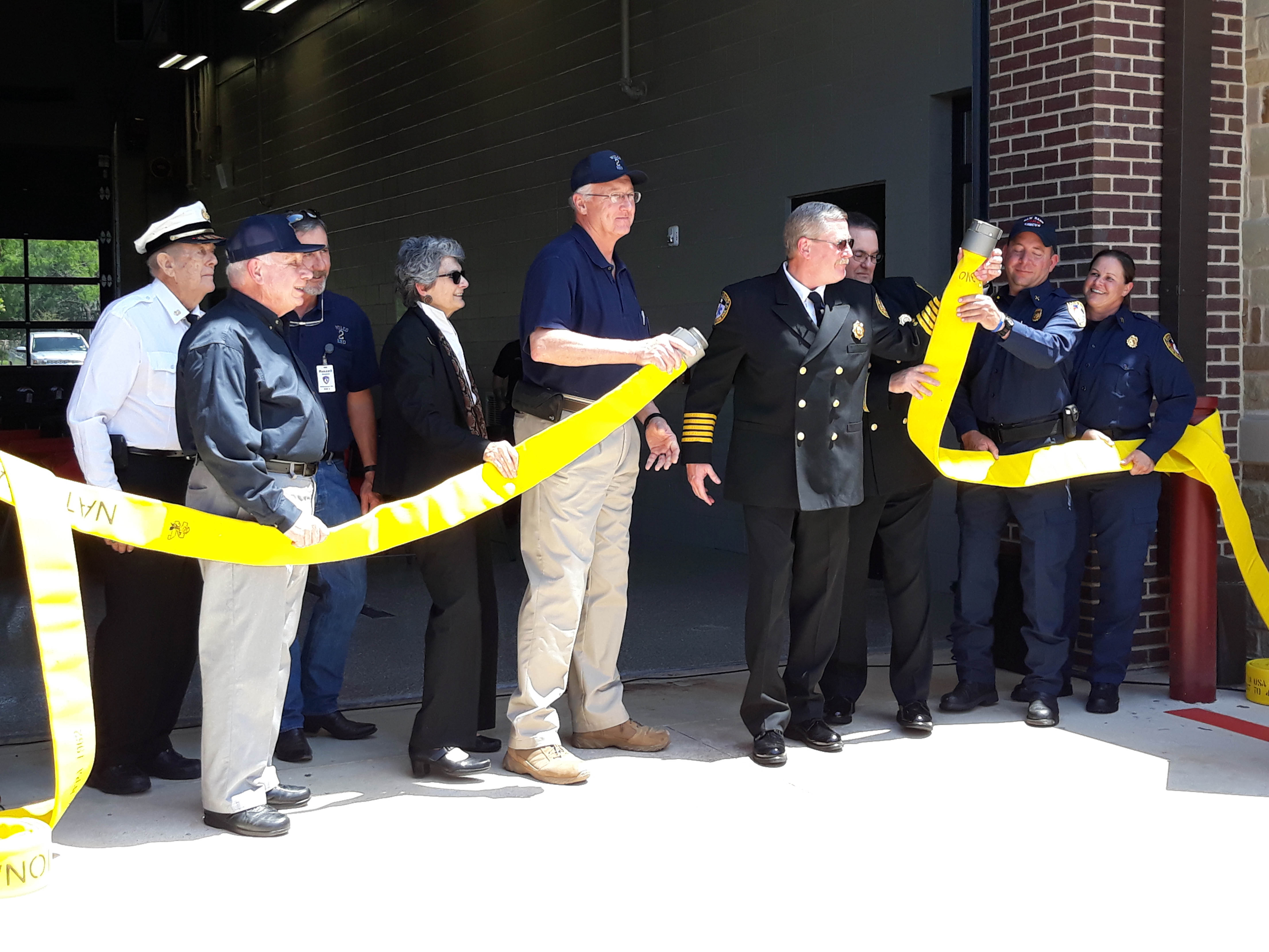 Participating in the traditional fire hose uncoupling during the ESD 2 grand opening were left to right Bob Steinmann, Former Chief, Sam Bass Fire Department; Darryl Pool, ESD2 Secretary; Russel Strahan, ESD2, Vice President; Commissioner Cook; Thomas Nanninga, ESD2 President; and Sam Bass Fire Department Chief David Kieschnick, Assistant Chief Keith Farris, Captain James Shofner and Captain Amber Jordan.