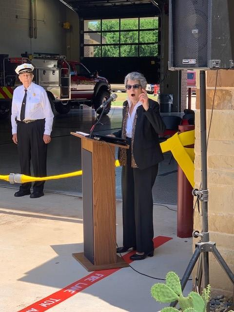 Commissioner Cook speaks at the podium and behind her is former Fire Chief Bob Steinman listening.