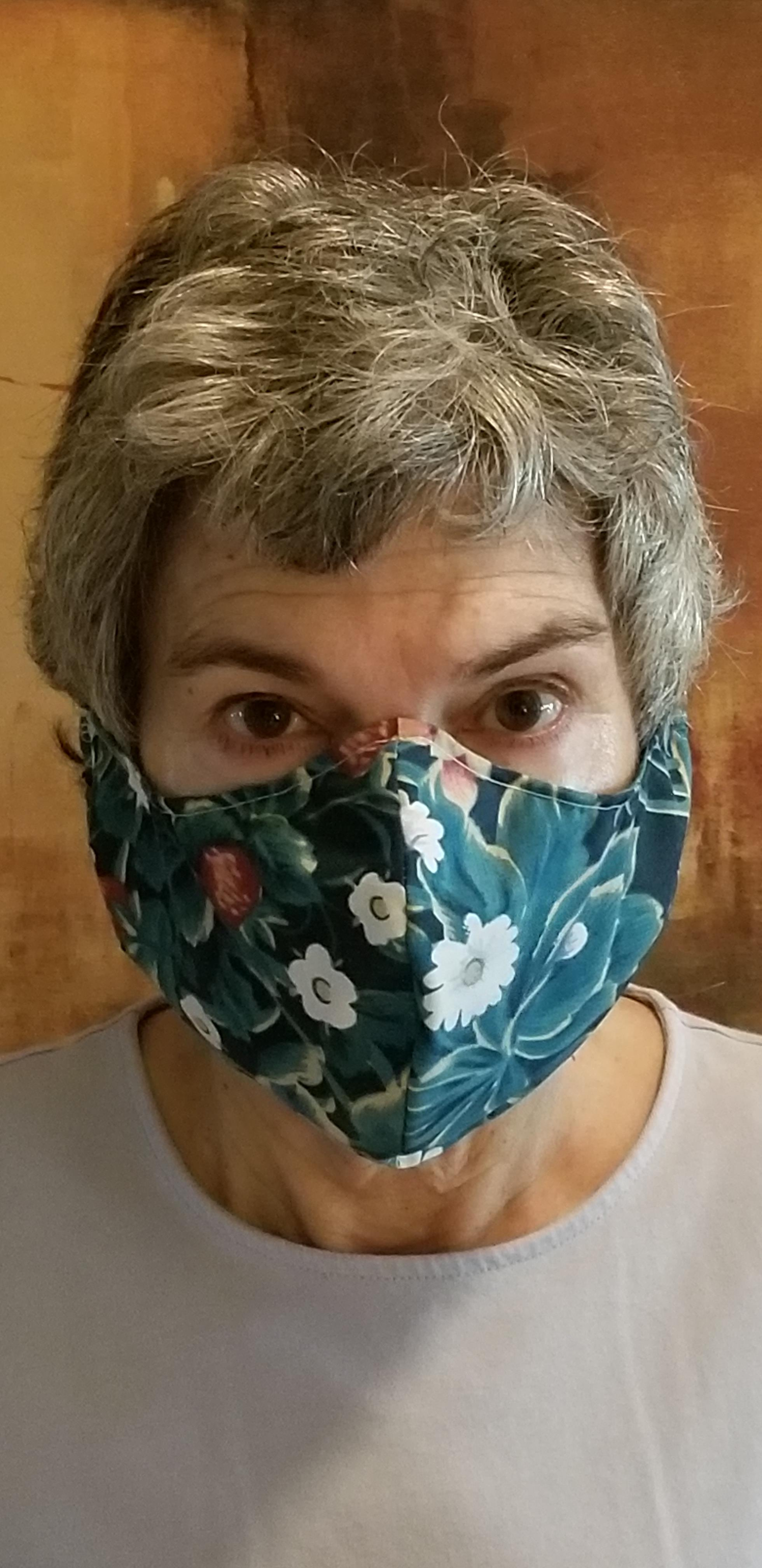 Commissioner Cook is wearing a face mask with floral print that she handmade.