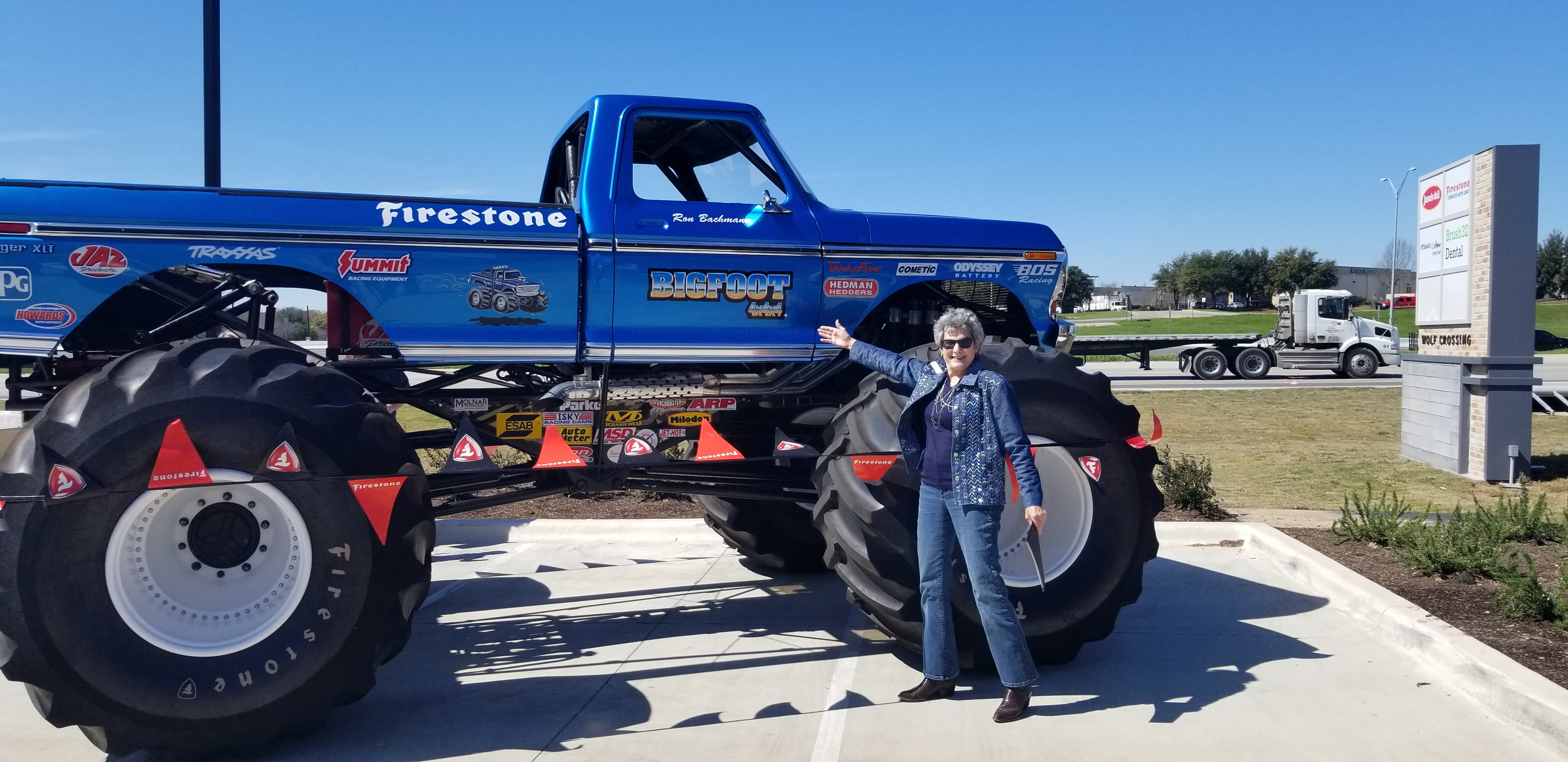 Commissioner Cook stands in front of the blue Firestone monster truck that is now retired.