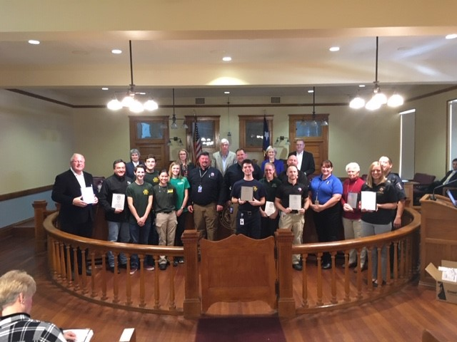 Volunteers stand at the front of the courtroom with County Commissioners and County Emergency Management Staff after receiving honorary certificates for their contributions.