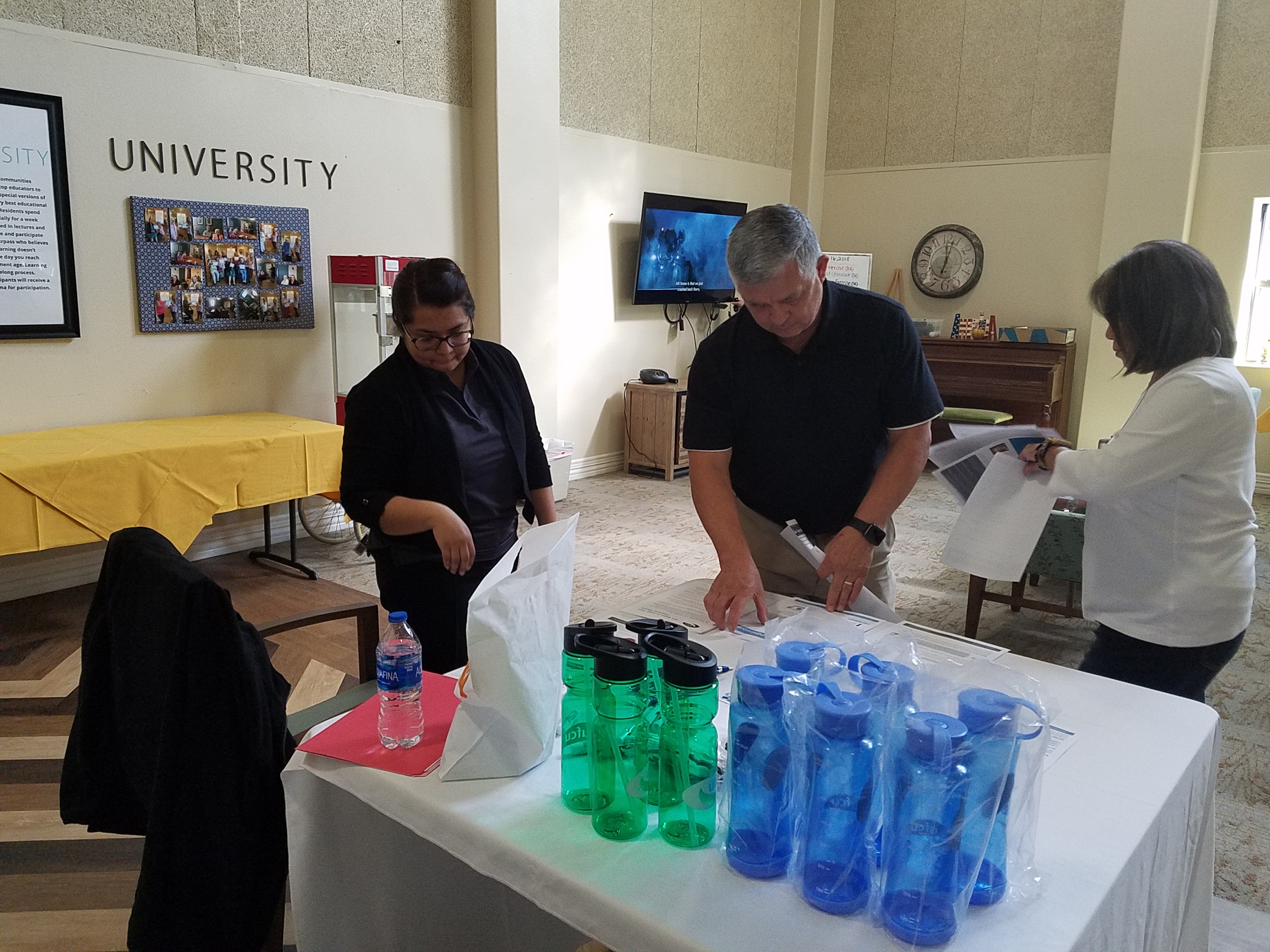 Tony Rosas with University Federal Credit Union sets up their display with Reina Morales and his wife, Gail, prior to his presentation on banking safety.