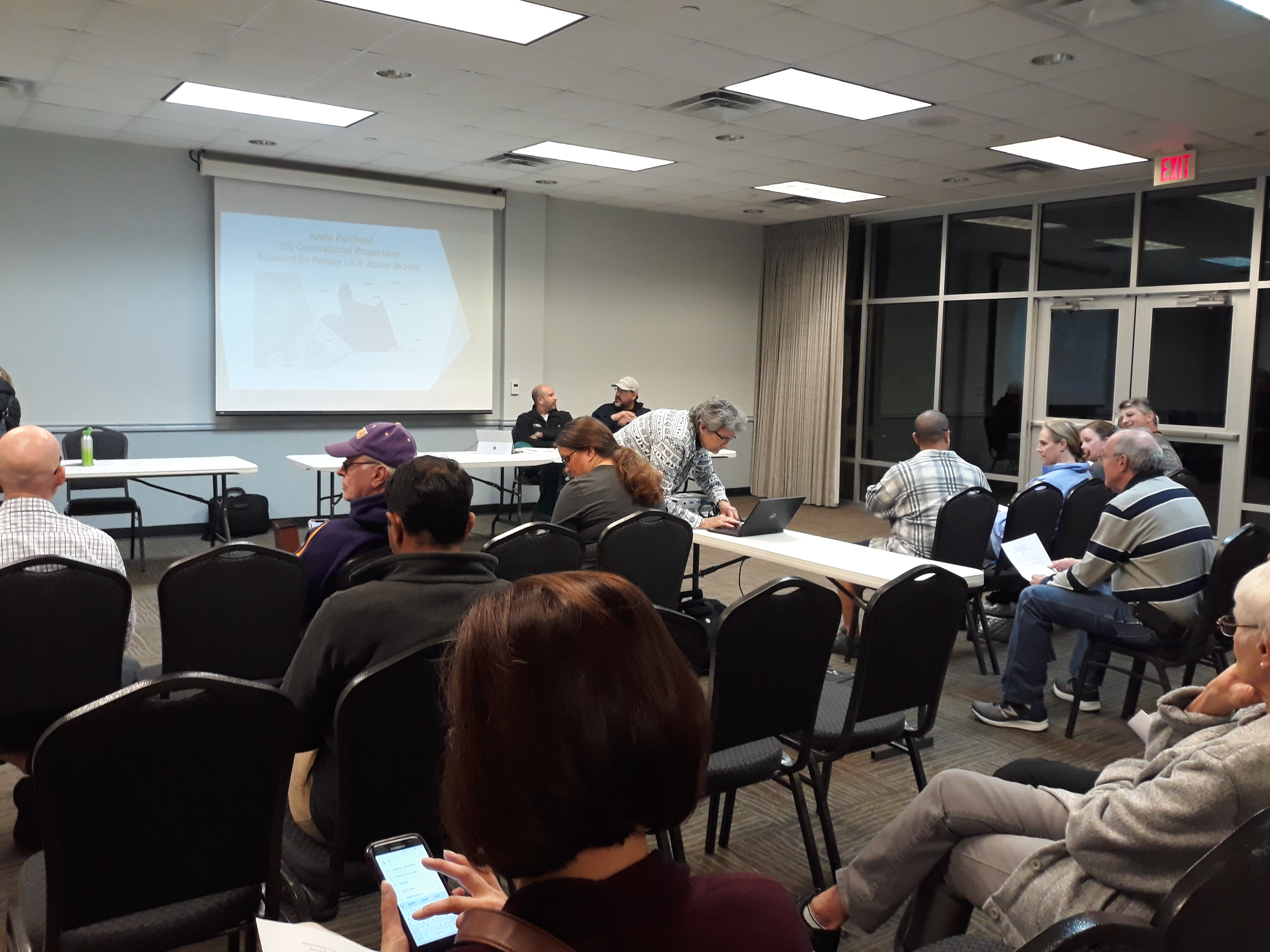 Commissioner Cook prepares the projector for her PowerPoint presentation. Seated are HOA residents and at the front table (lf) President Vinnie Choudry and (rt) Treasurer Fernando Espinosa.