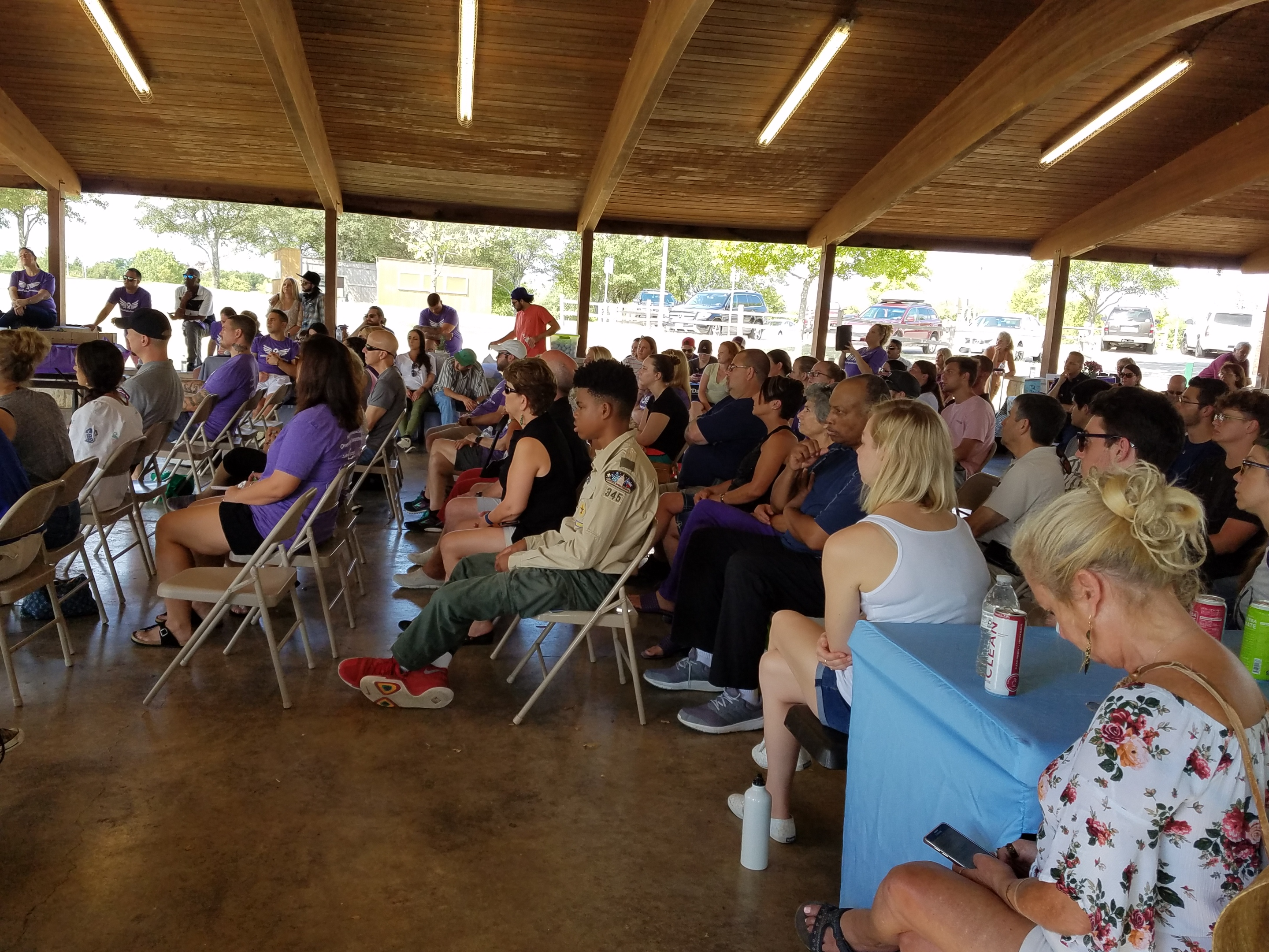A large group of people are seated beneath the Lakeview Pavilion at Old Settlers Park listening to various speakers.