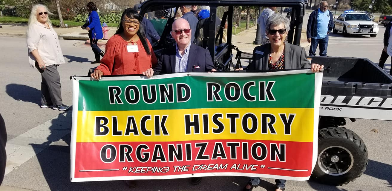 Commissioner Cook along with Tina Steiner and Rich Parson, local Round Rock residents and advocates, hold a banner during the MLK walk that reads Round Rock Black History Organization.