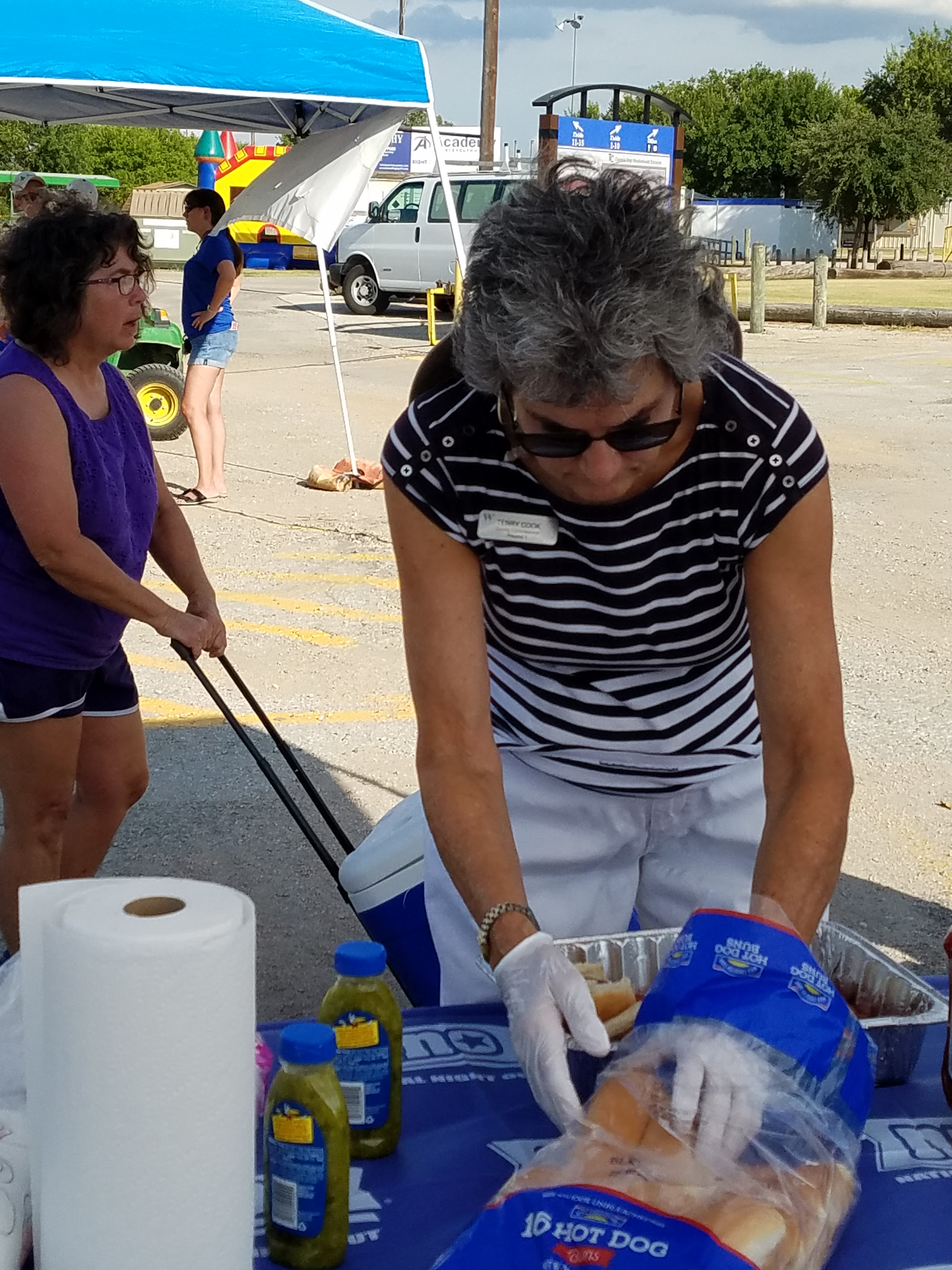 Commissioner Cook is preparing hot dogs to serve the attendees.