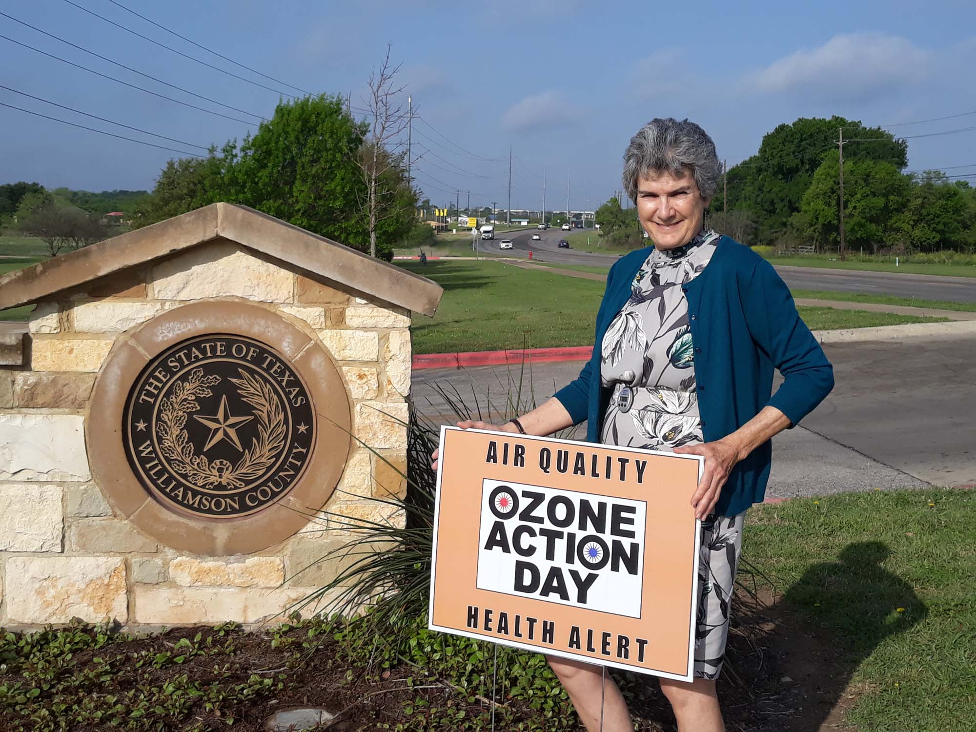 Commissioner Cook is holding her Ozone Action Day sign in front of the entrance to the Williamson County Jester Annex in Round Rock.