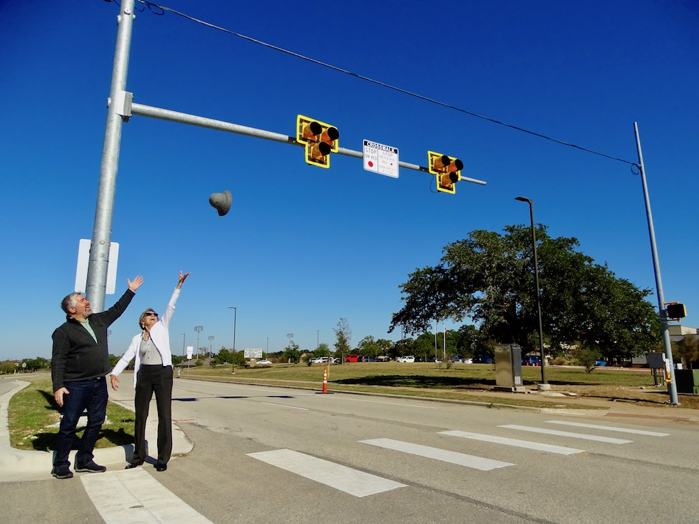 Standing alongside Dist. 6 Austin City Council Member Jimmy Flannigan, Commissioner Cook tosses her hat into the air to celebrate the new PHBs and improved safety for students.