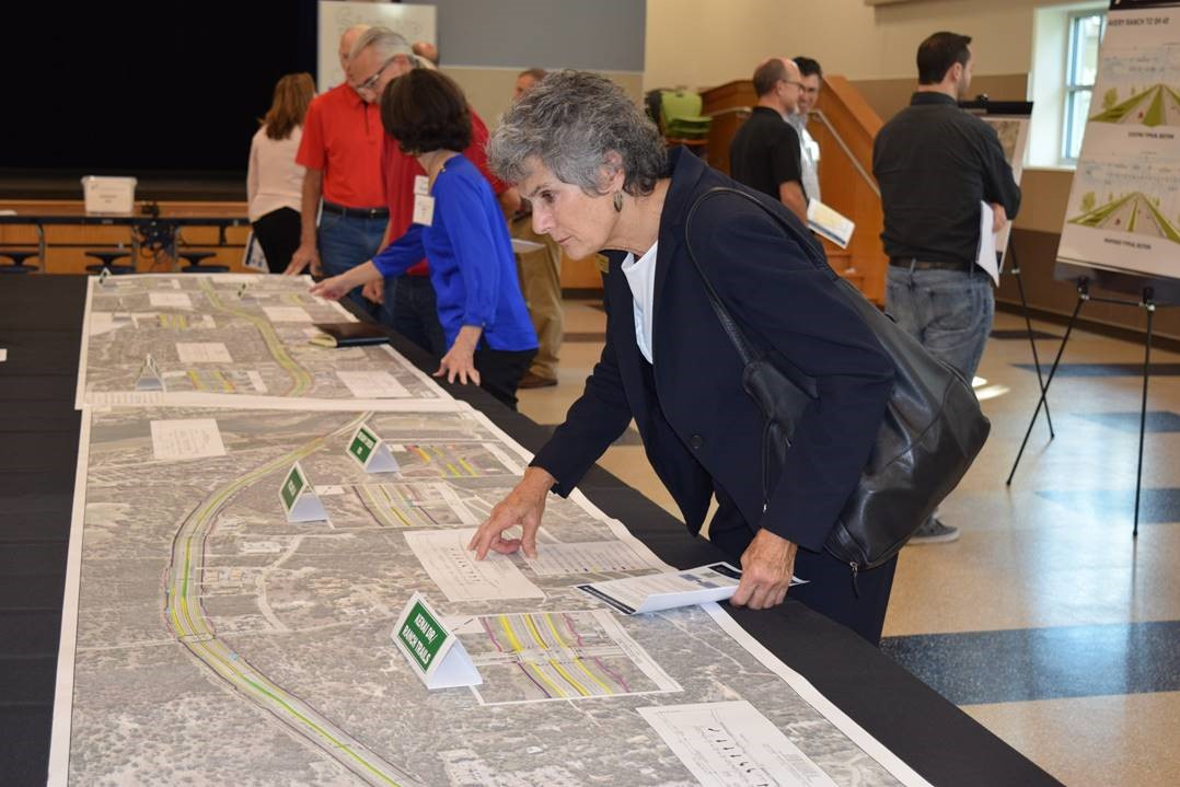Commissioner Cook studies schematic drawings on a long table depicting the entire Parmer Lane expansion project proposal.