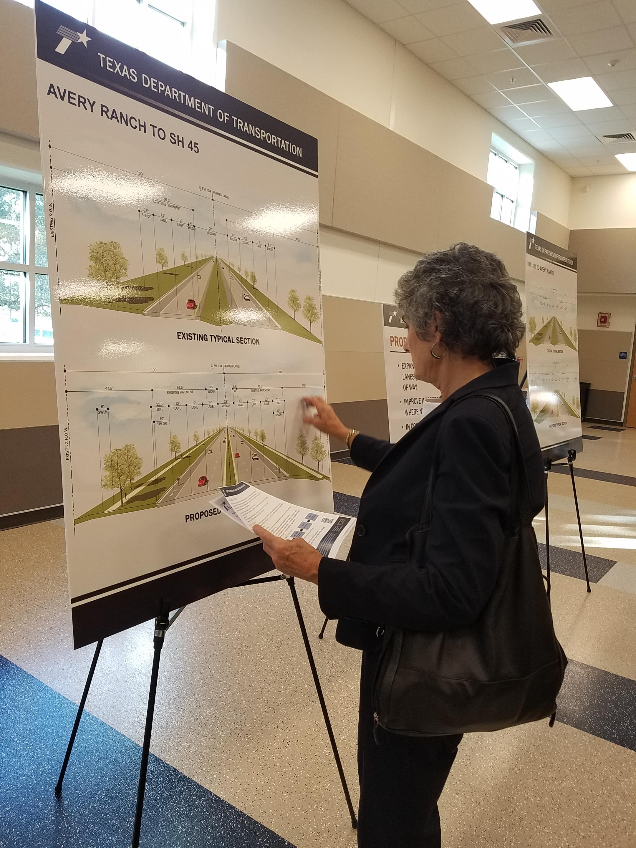 Commissioner Cook studies a chart with the proposed expansion from Avery Ranch to SH 45.