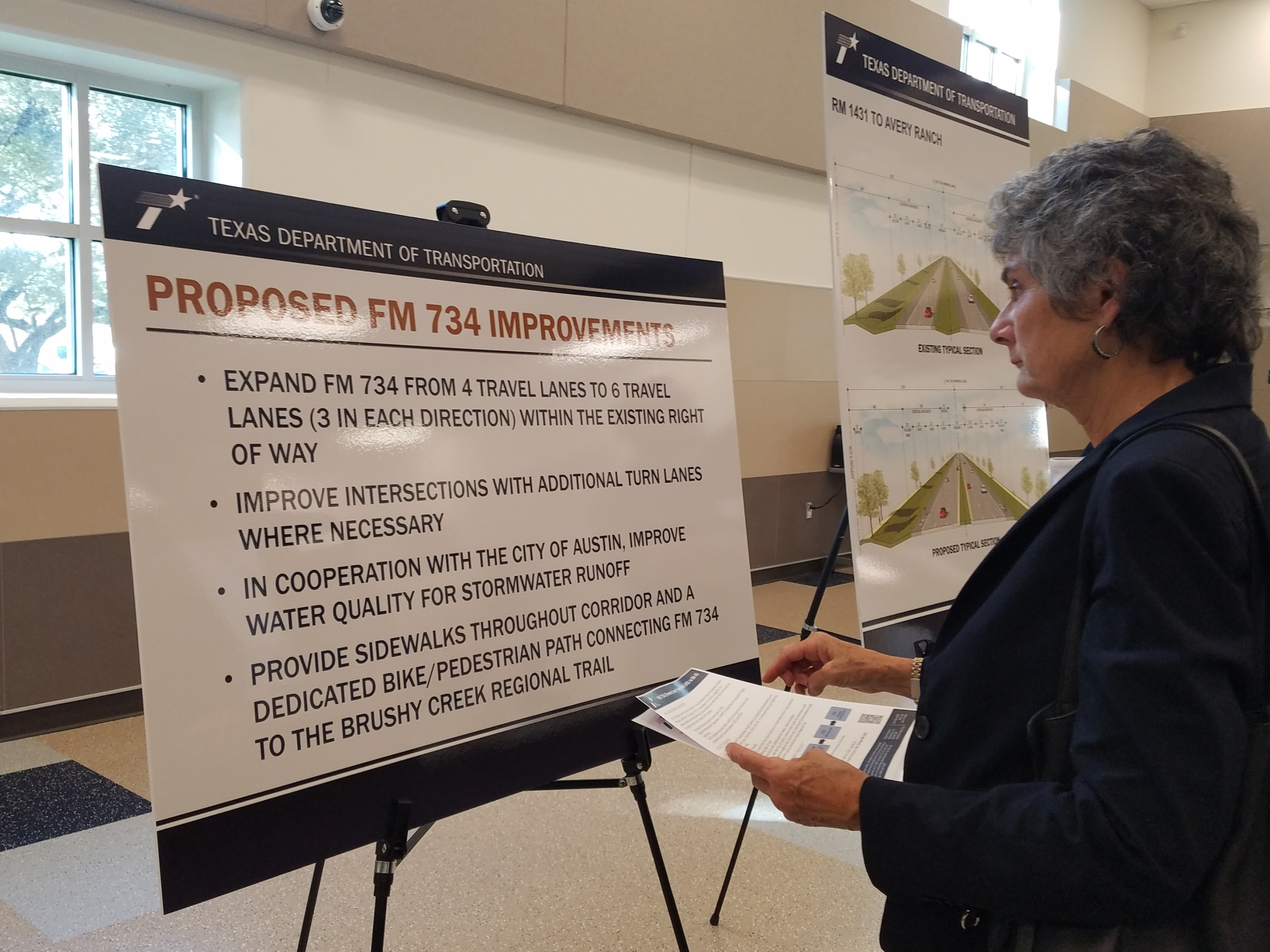 Commissioner Cook reviews a chart with the proposed project plans.