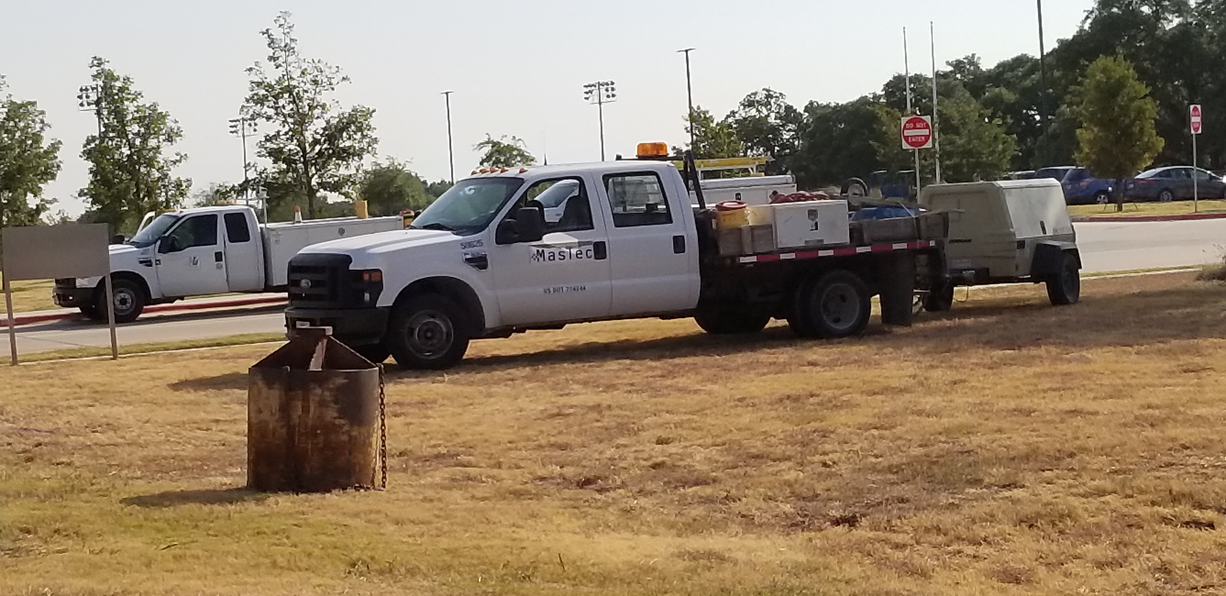 Mastec trucks are parked while crews begin work on the power pole and pedestrain beacon.
