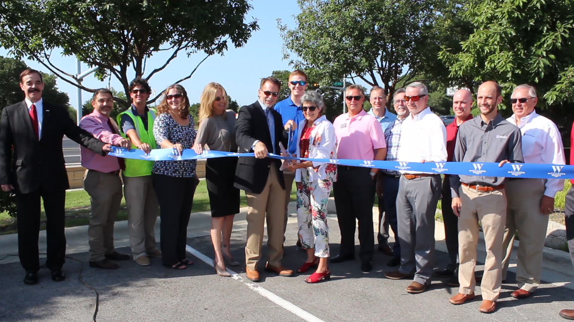 A group of attendees involved with the completion of RM 620 holds the ribbon as Commissioner Cook cuts it with large scissors amidst a backdrop of trees and the road behind them.