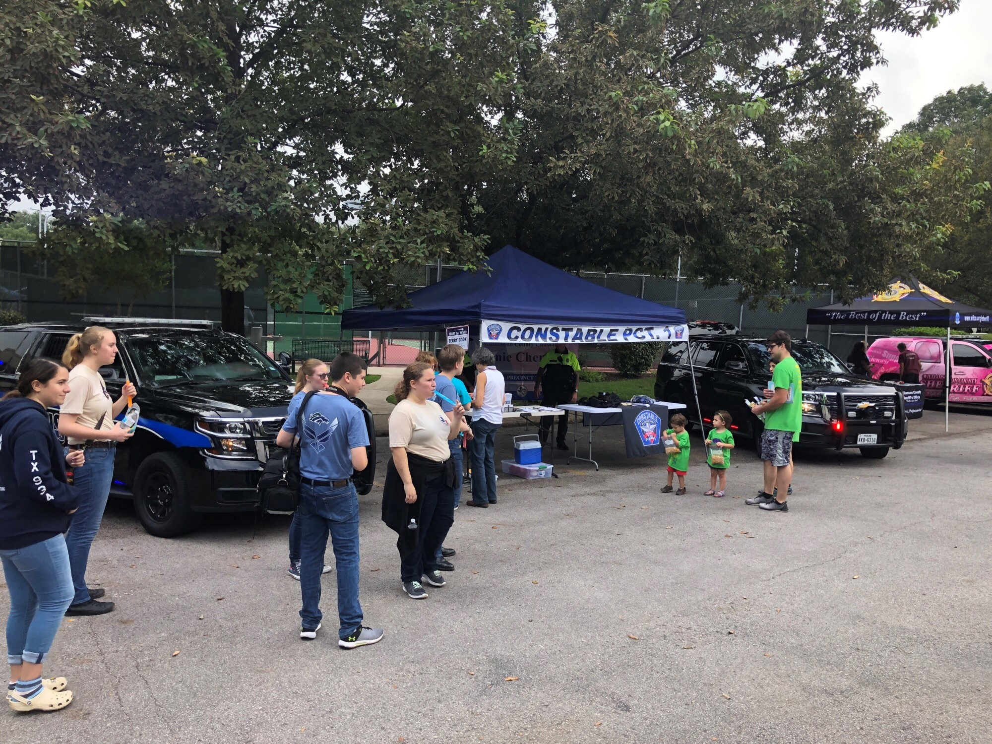 Visitors to Rattan Fest are milling around Constable Vinnie Cherrone's booth and canopy, while Commissioner Cook reviews handouts right before the rain started.