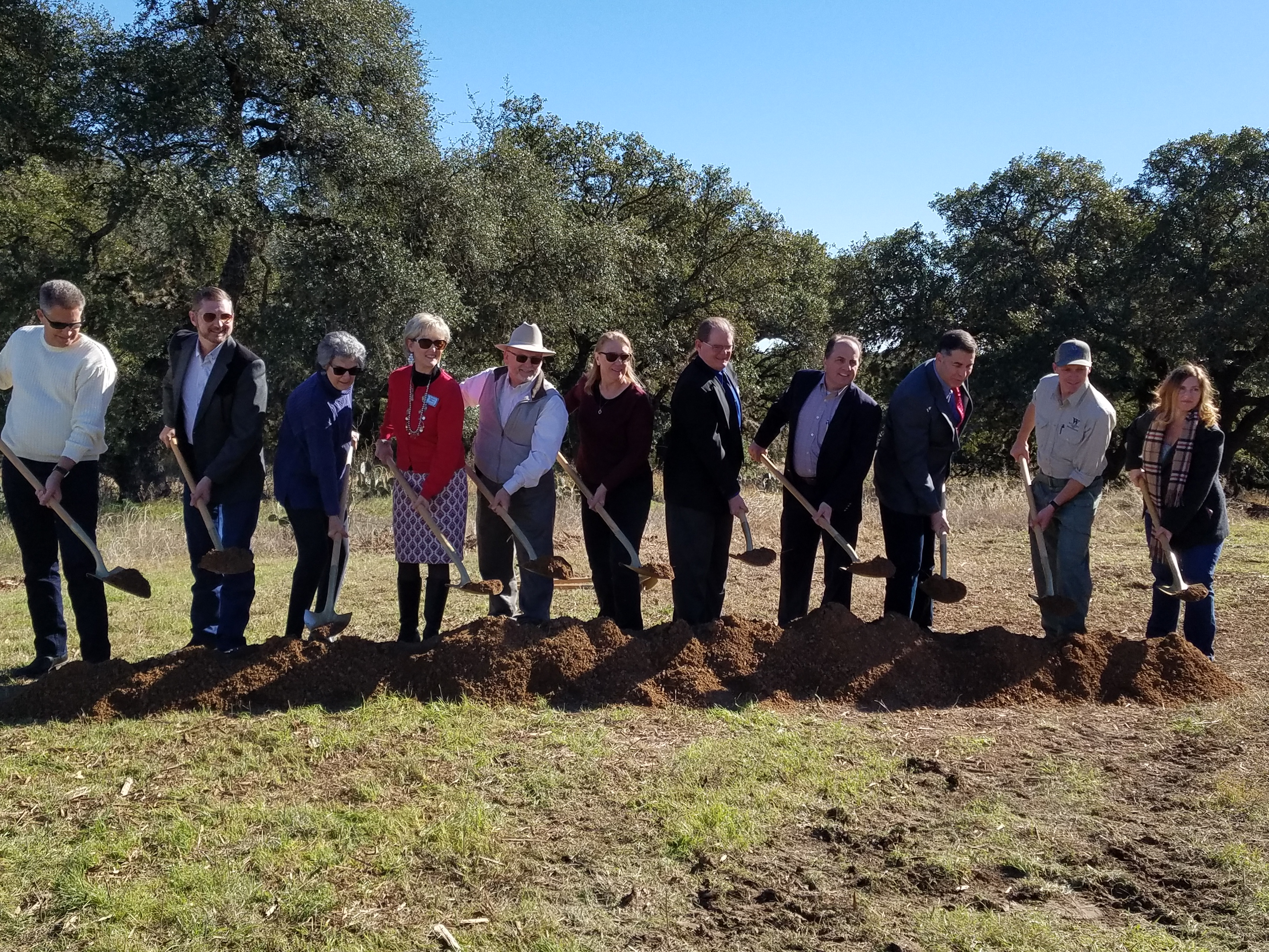 A group of city and county officials, as well as those involved with developing the park, dig up dirt with their shovels to officially break ground for River Ranch Park.
