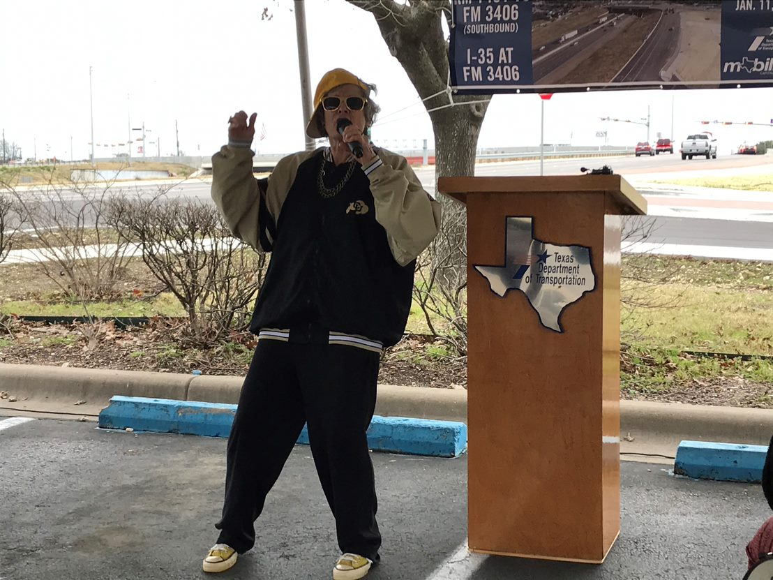 "Commissioner Cook Performs her Rap ""Yo, Flatiron"" outside on Denny's parking lot with I-35 in the background."