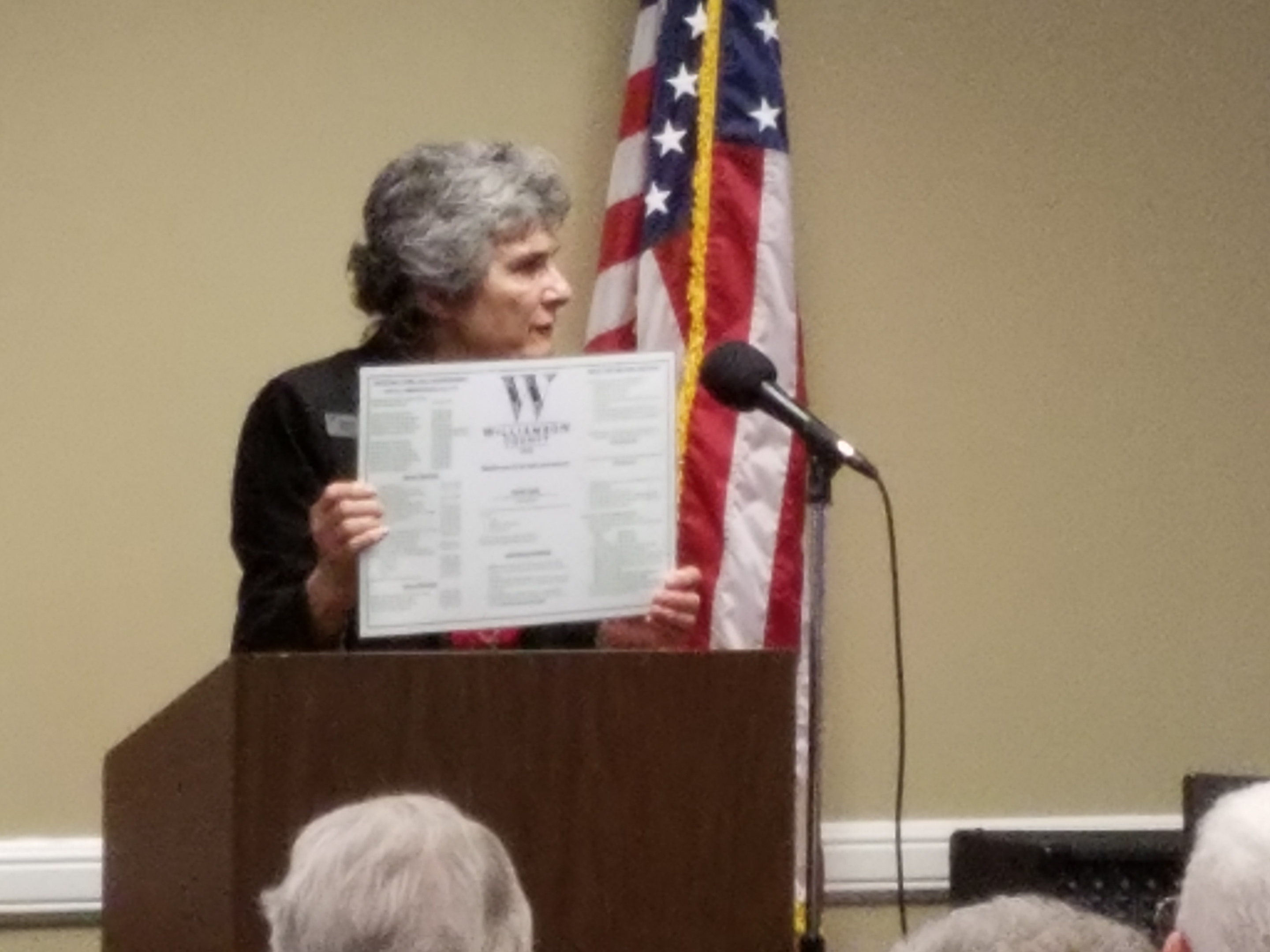 Commissioner Cook holds up the back side of a placemat standing at the podium.