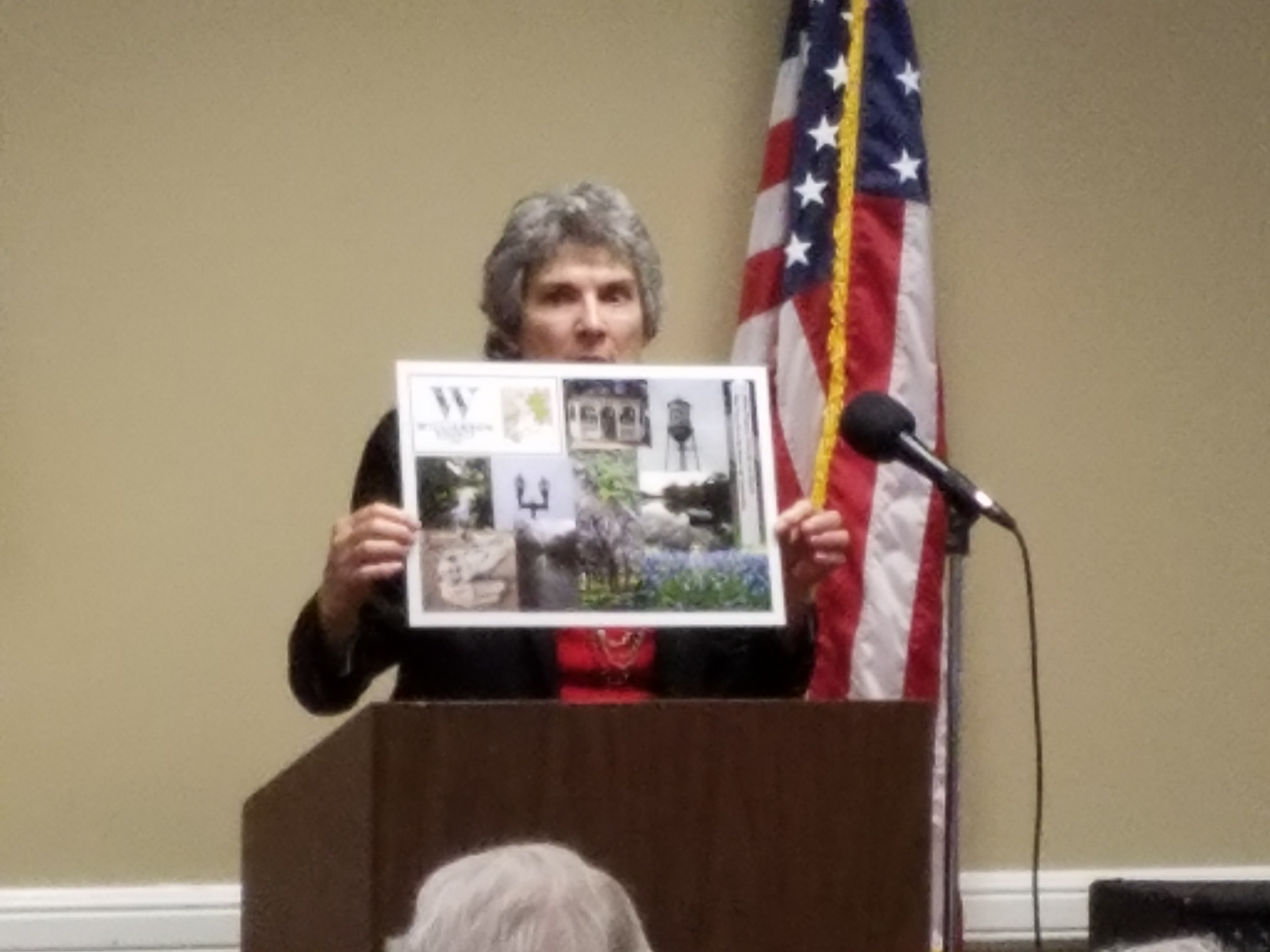 Commissioner Cook holds up the front side of a Senior Fraud Prevention Placemat.