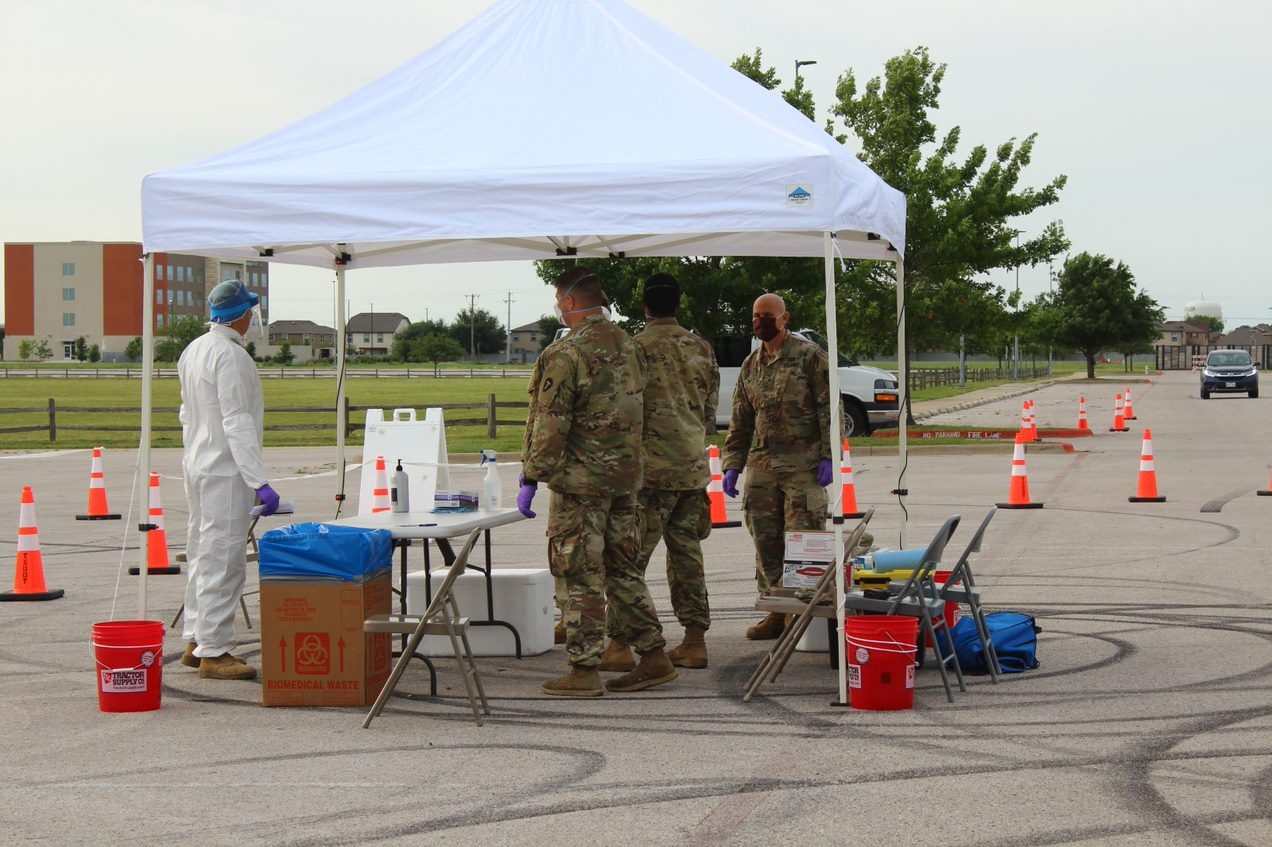 Members of the Texas National Guard and a medical professional in white personal protective equipment stand beneath a white canopy before people begin arriving to be tested.