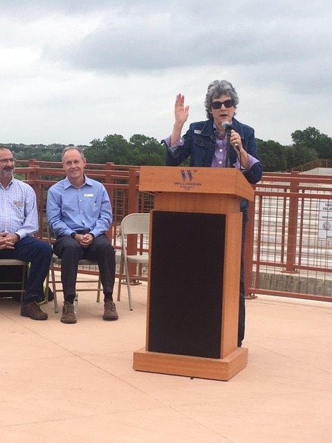 Commissioner Cook speaks with a mic at a podium outside at Dam 7 with two people sitting behind her.