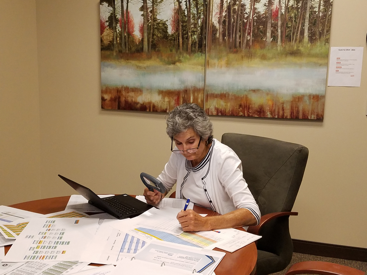 Commissioner Cook Cook sits at her office desk in front of her laptop with magnifying glass in one hand and pen in the other as she reviews and analyzes budget requests from county departments