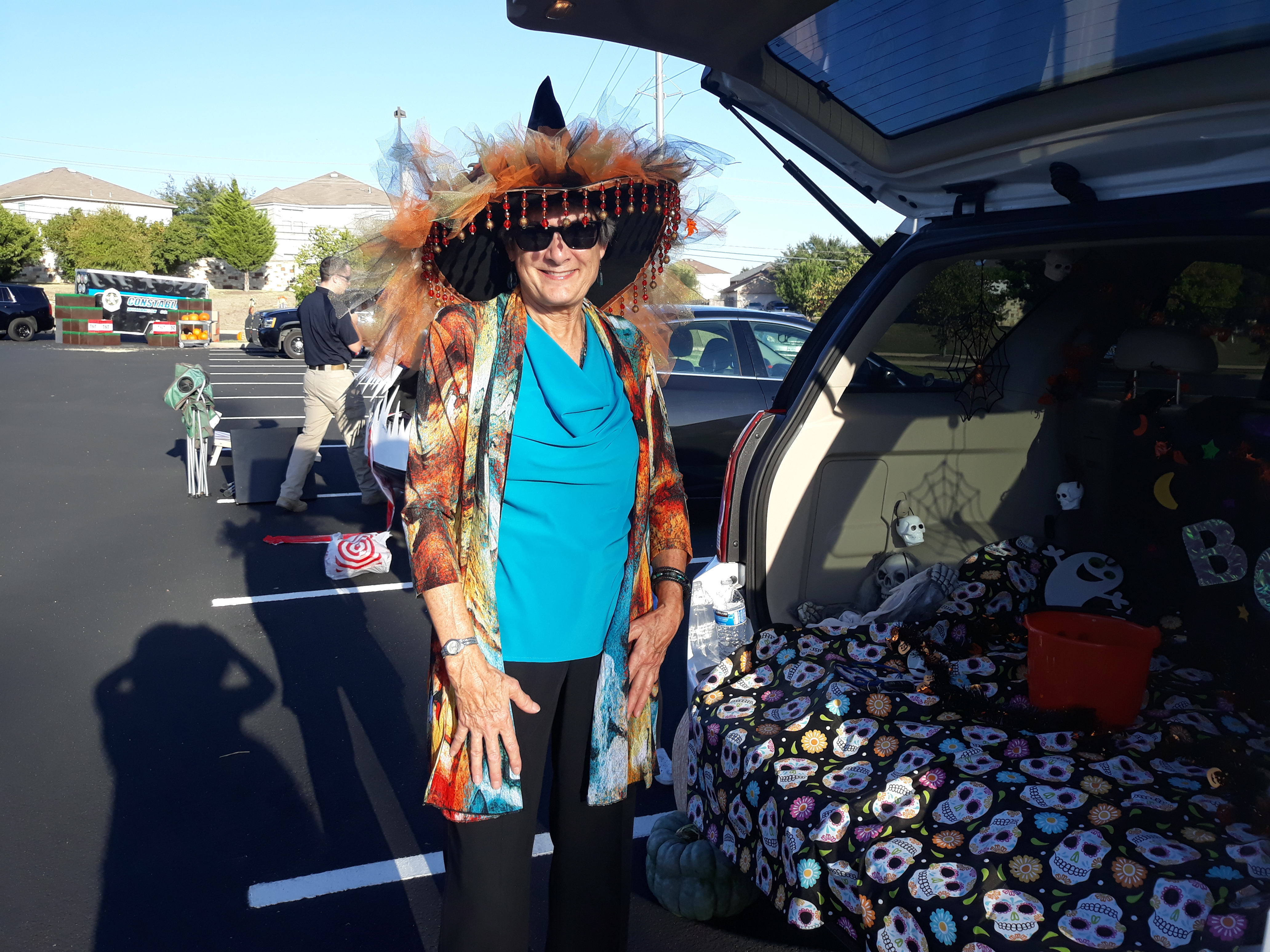Commissioner Cook is wearing her richly decorated witch's hat from a previous event and is standing next to staffer Doris Sanchez's decorated vehicle.