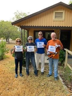 Left to Right are staff member Doris Sanchez, Commissioner Cook, HEB employee and Round Rock resident Frank Valle, and staff member Garry Brown holding United Way signs before the work of cleaning up the yard began.