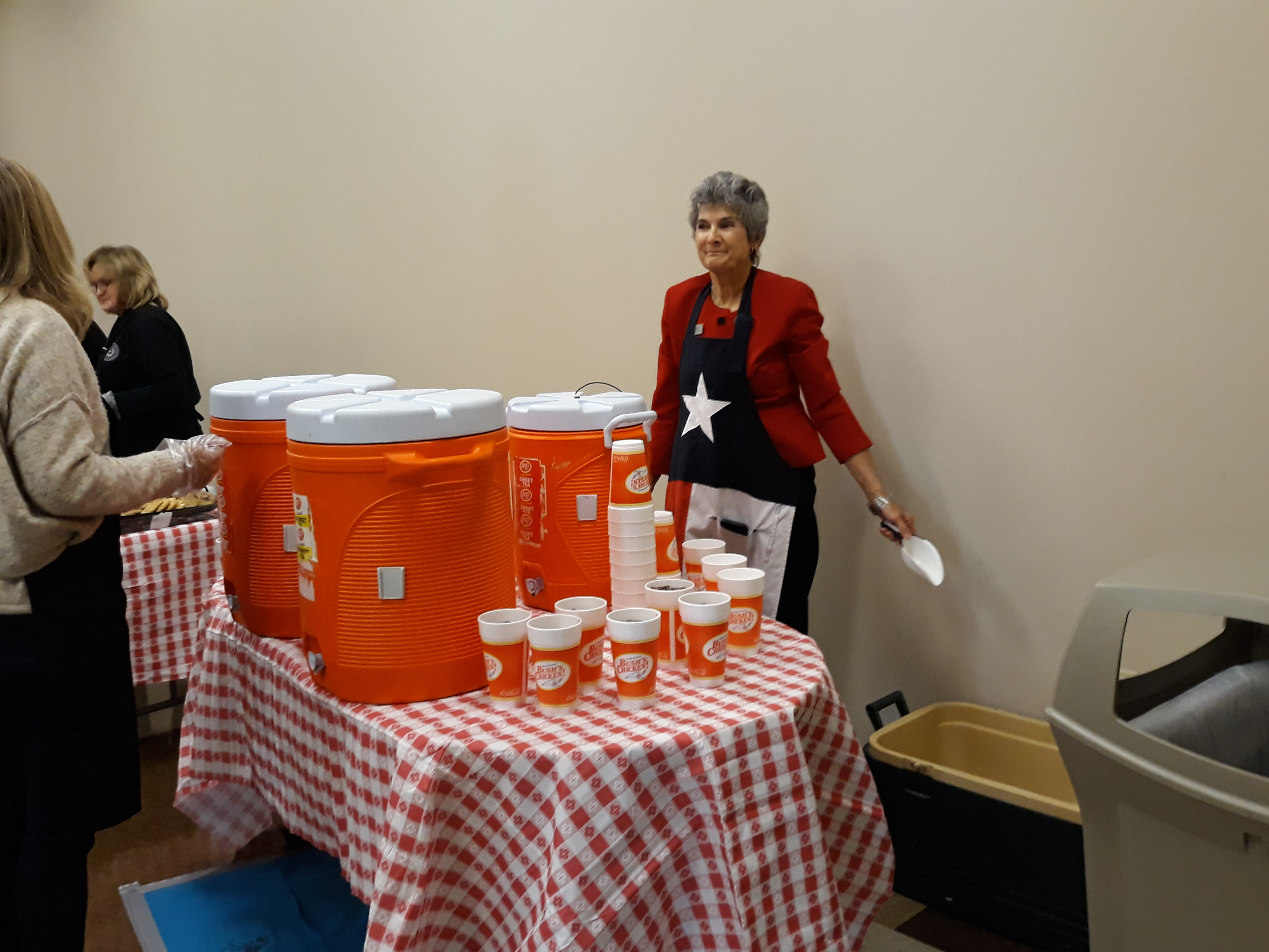 Commissioner Cook waits behind the large orange dispensers with white lids to refill glasses with sweet and unsweetened tea.