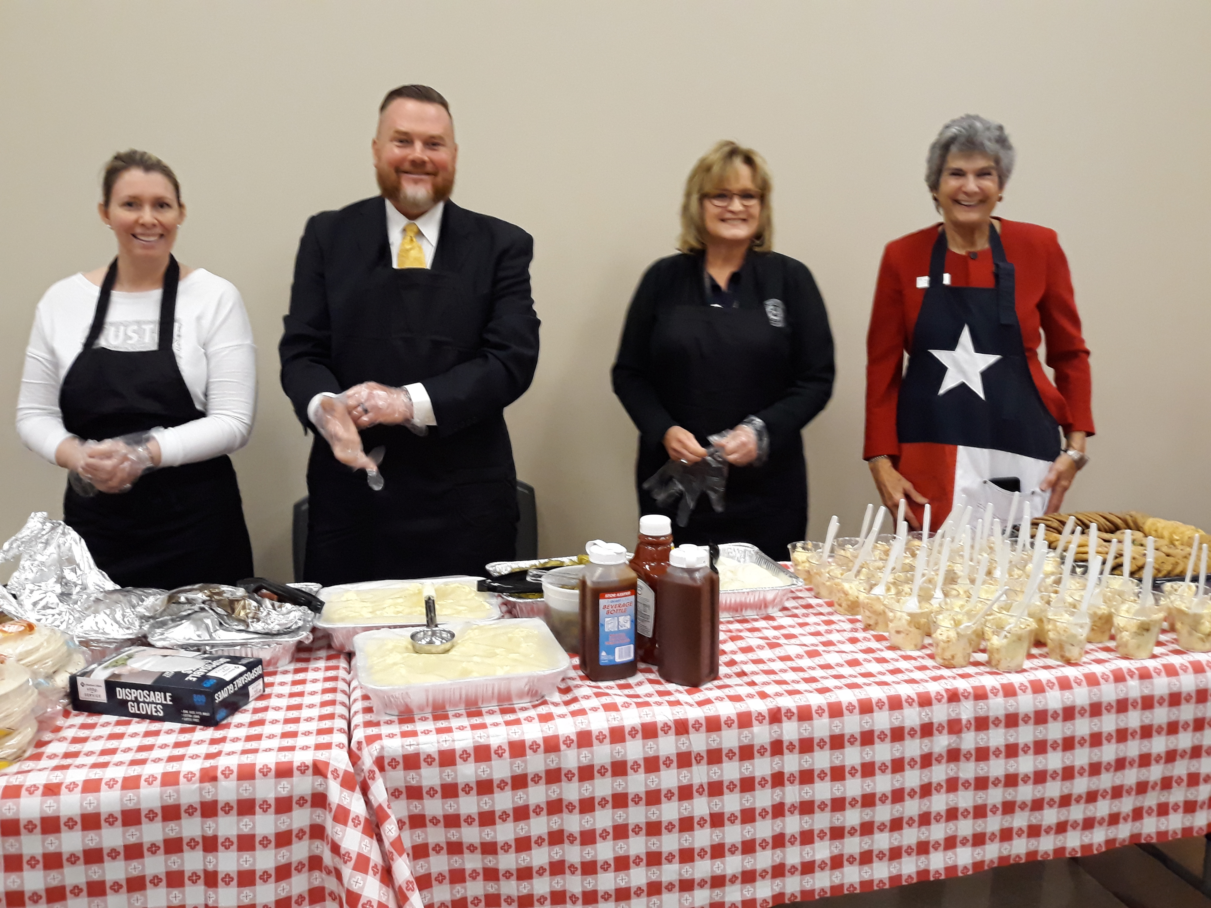 "Wearing aprons and donning plastic gloves to serve the veterans lunch (lf to rt) are Rachel Arnold from Pct. 2 Commissioner Valerie Covey's Office; County Attorney Doyle ""Dee""  Hobbs; District Clerk Lisa Adams; and Commissioner Cook."