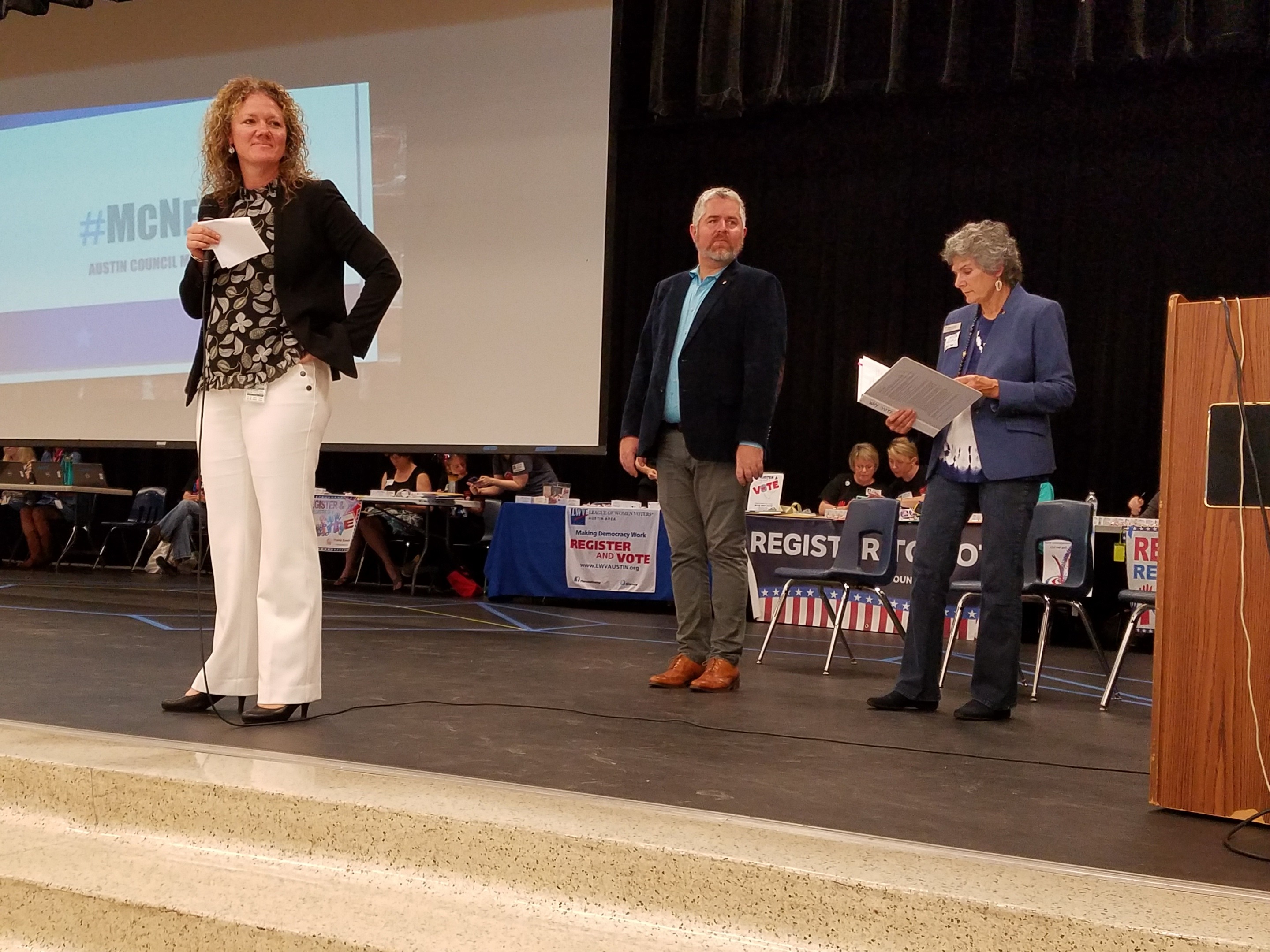 Principal Amanda Johnson stands on stage waiting for students to find seats while Council Member Jimmy Flannigan and Commissioner Cook stand behind her.