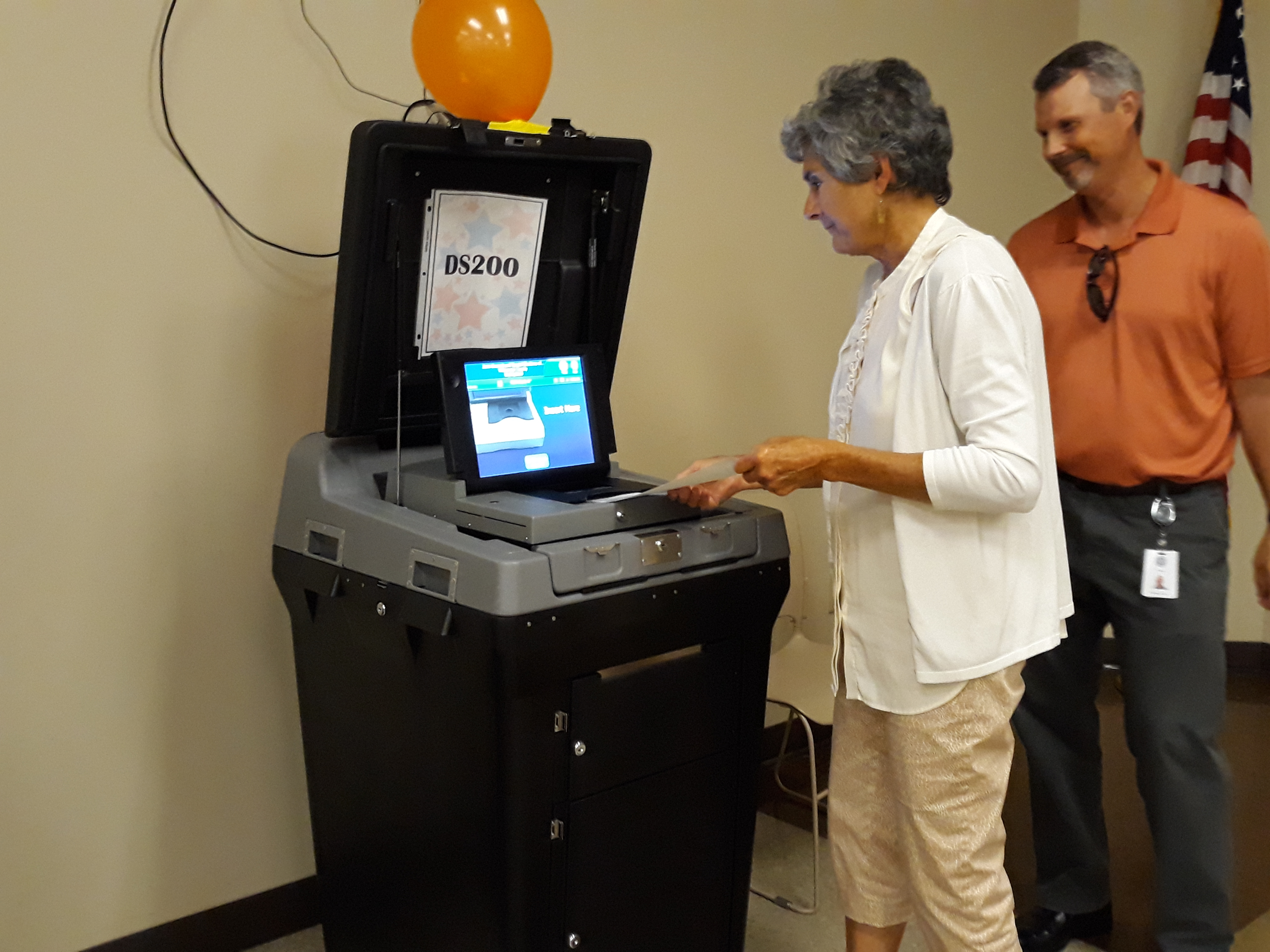 Commissioner Cook feeds her paper ballot to the scanning machine which will immediately show a message that she voted.