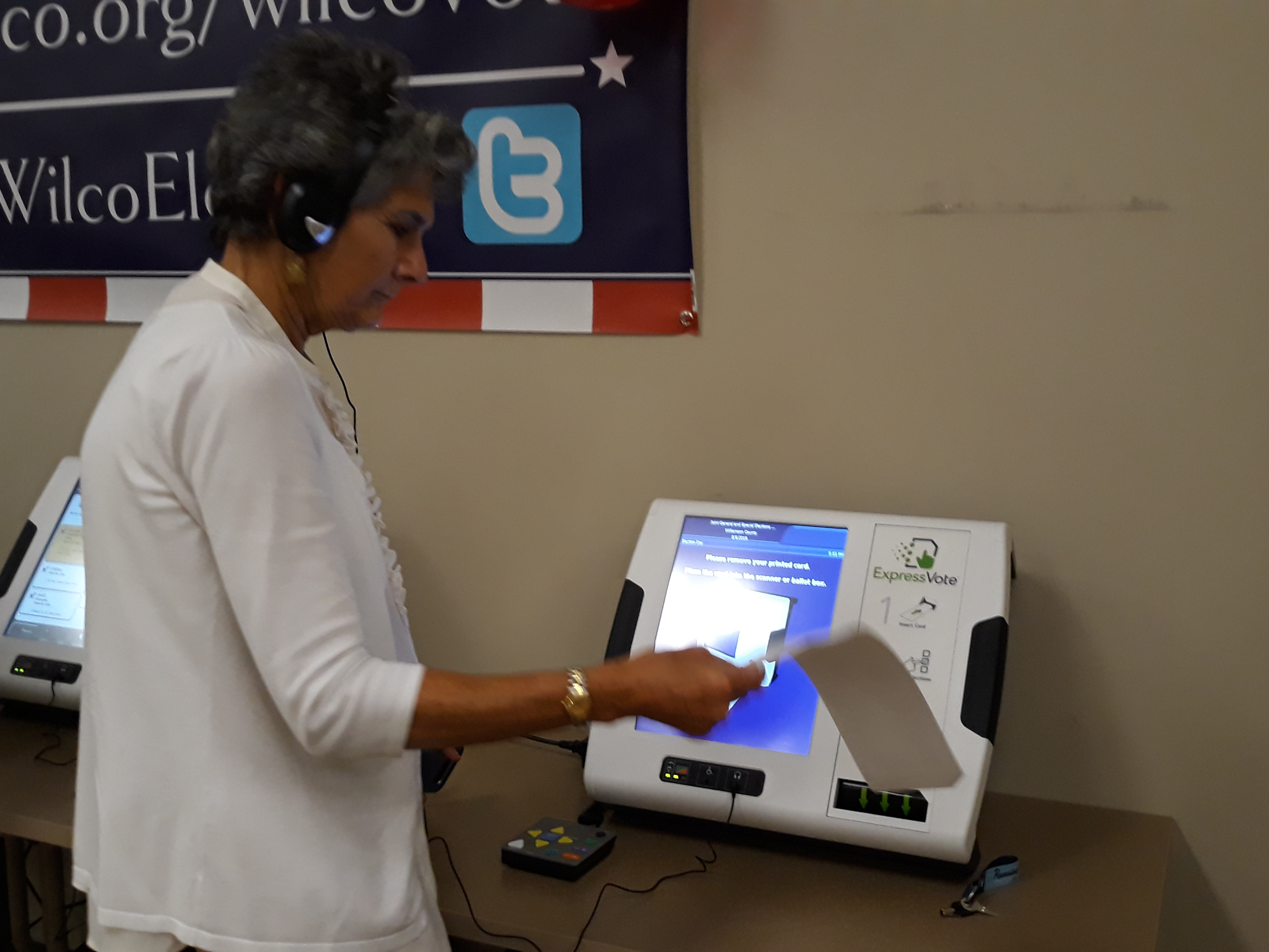 Commissioner Cook uses a headset for the hearing impaired as she reviews her paper ballot she receives after voting on one of the new machines.