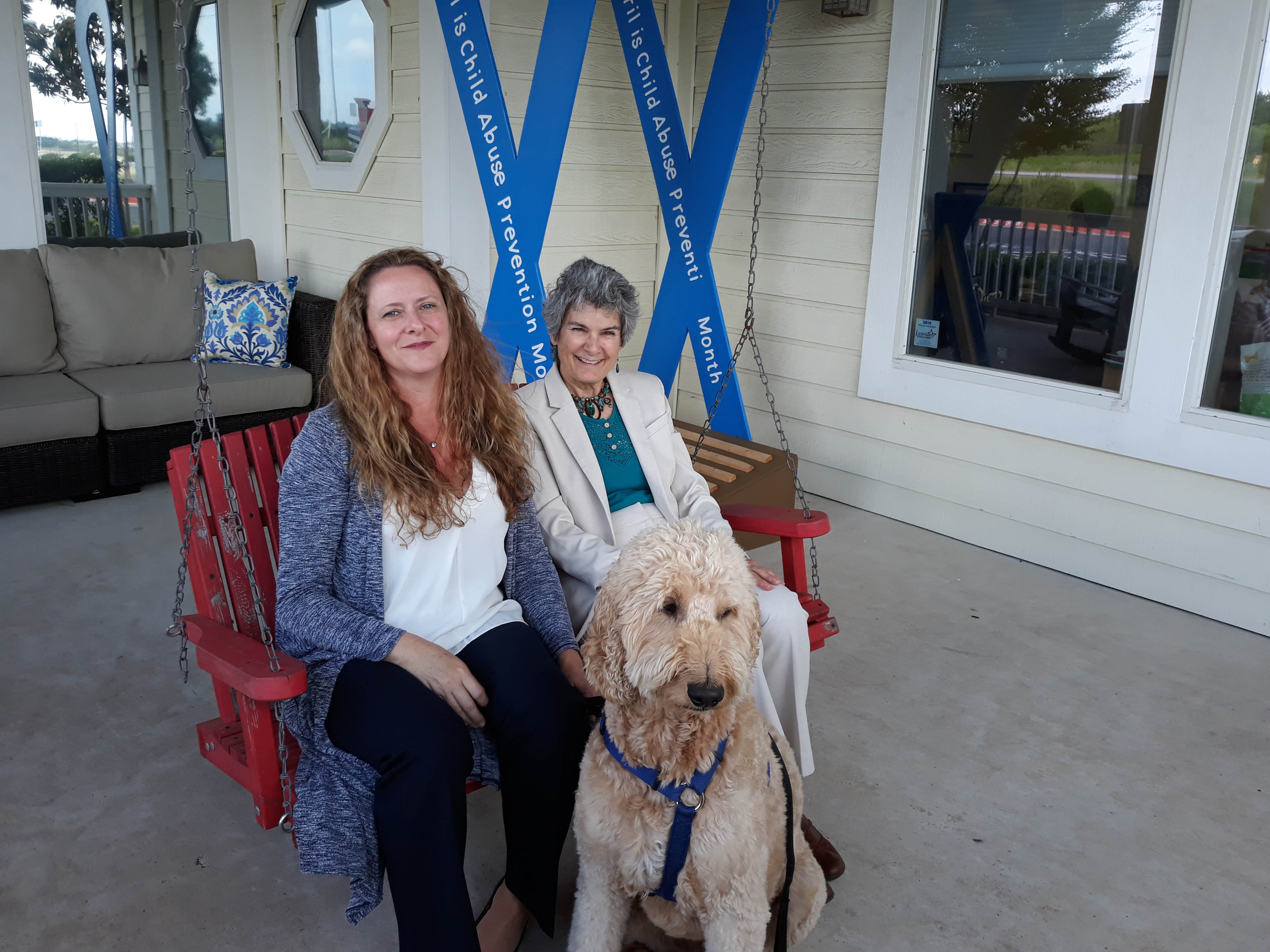 Commissioner Cook visits with CEO Kerrie Stannell on the proch of the Williamson County Children's Advocacy Center in Georgetown. They are joined by Charlie, the Golden Doodle, who calms the children with his peaceful and affectionate nature.